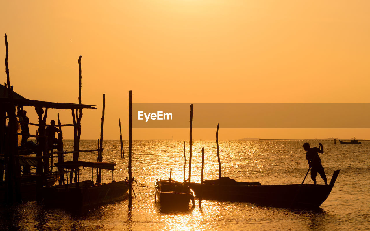 sunset, sky, silhouette, water, nautical vessel, orange color, transportation, mode of transportation, sea, beauty in nature, real people, nature, scenics - nature, lifestyles, men, clear sky, horizon over water, idyllic, copy space, outdoors, fisherman, wooden post