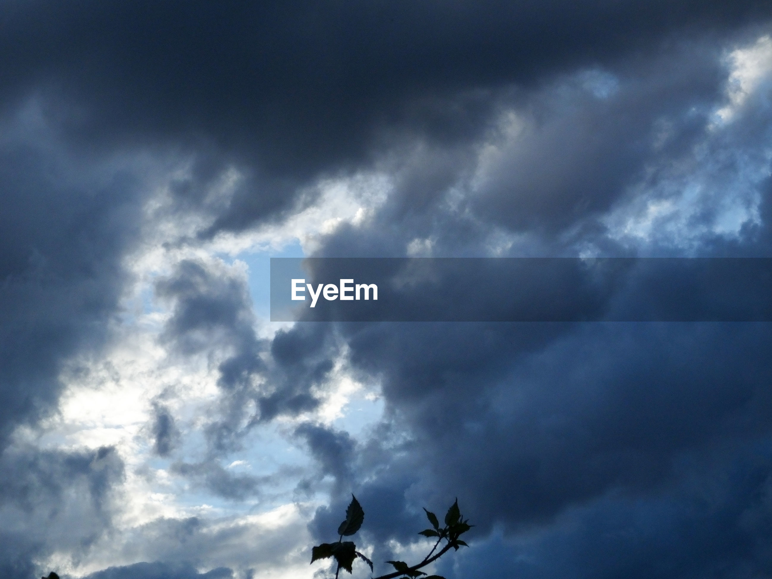 LOW ANGLE VIEW OF STORM CLOUDS IN BLUE SKY