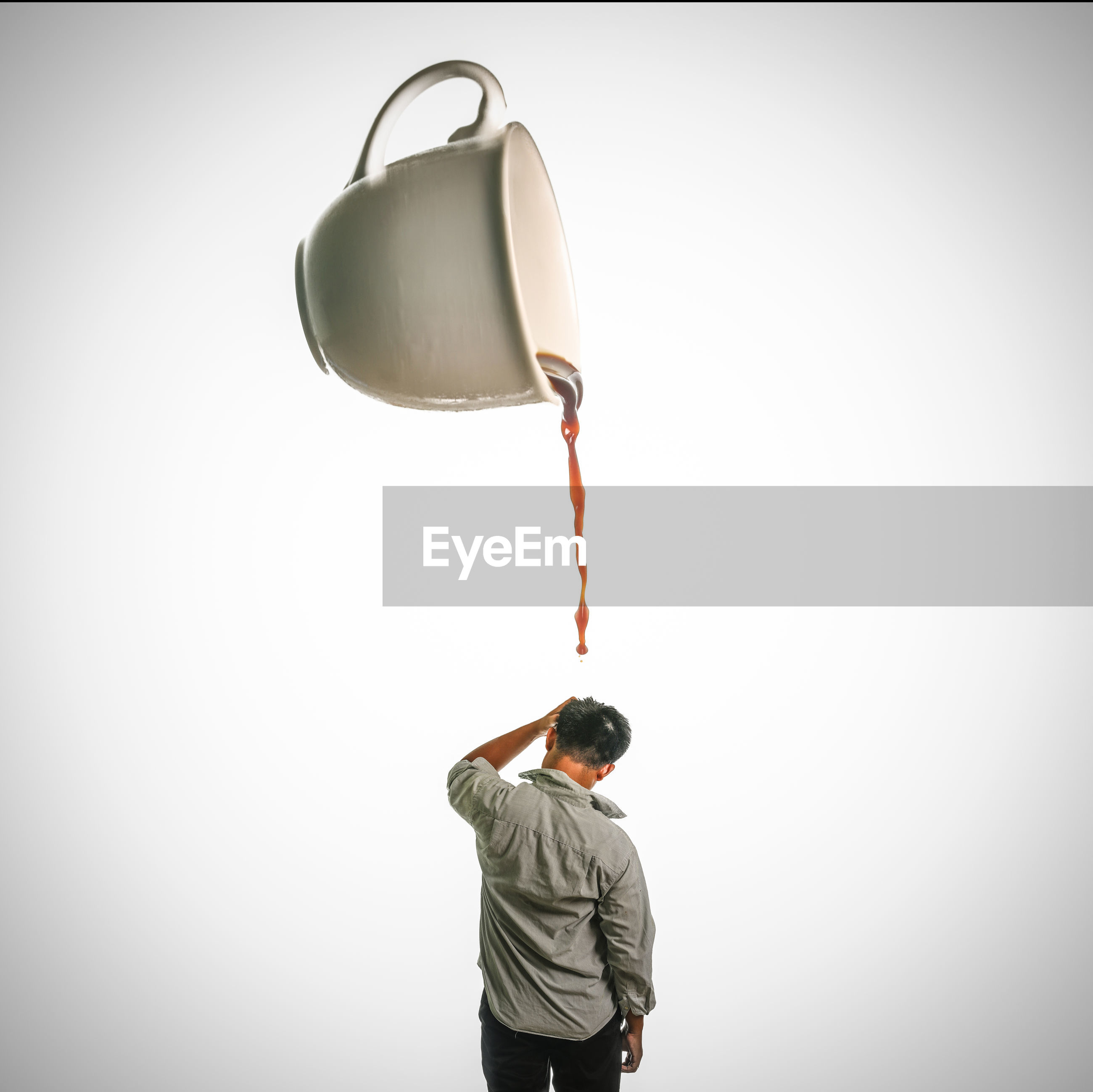 Optical illusion of cup pouring tea on man standing against white background