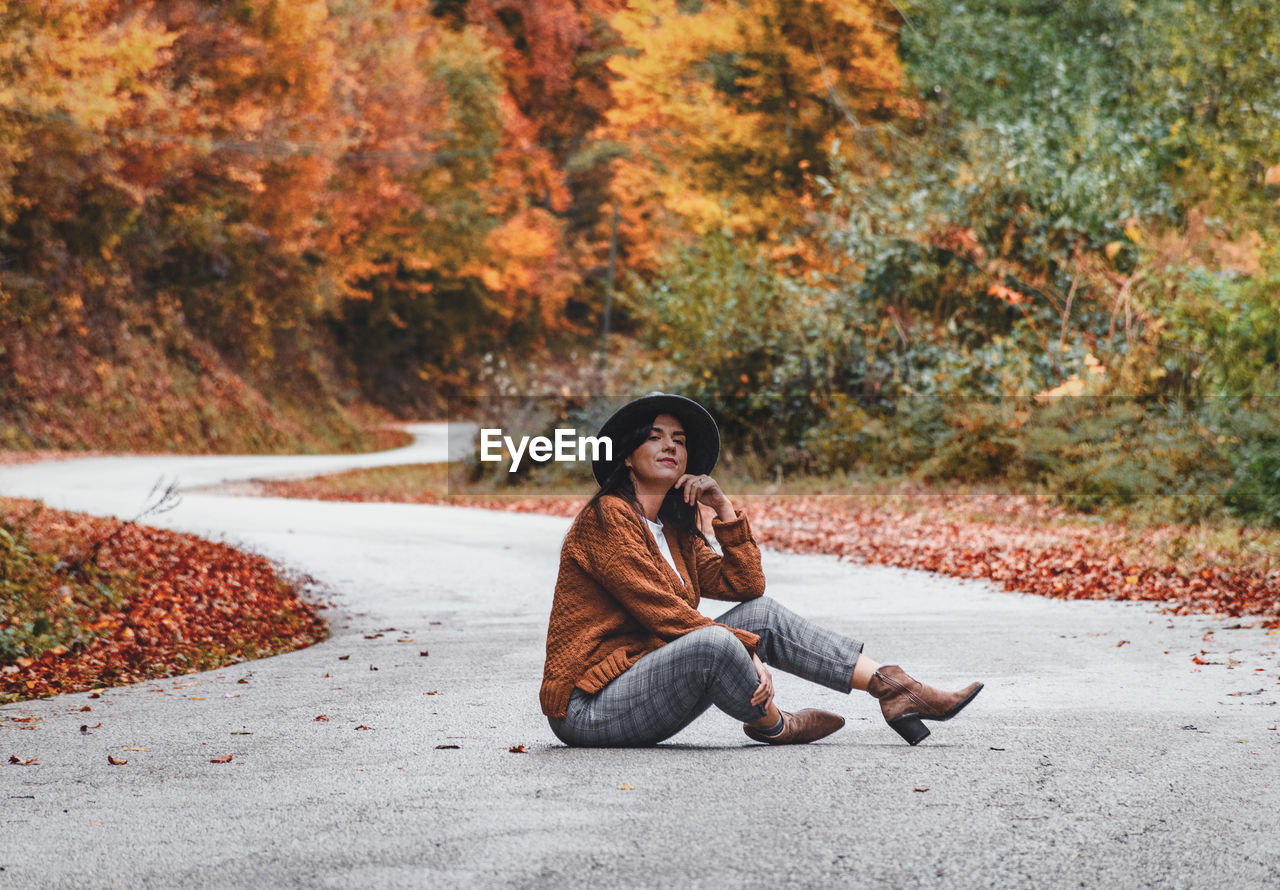 Young woman in autumn clothes sitting in the middle of road. fall colors, style.
