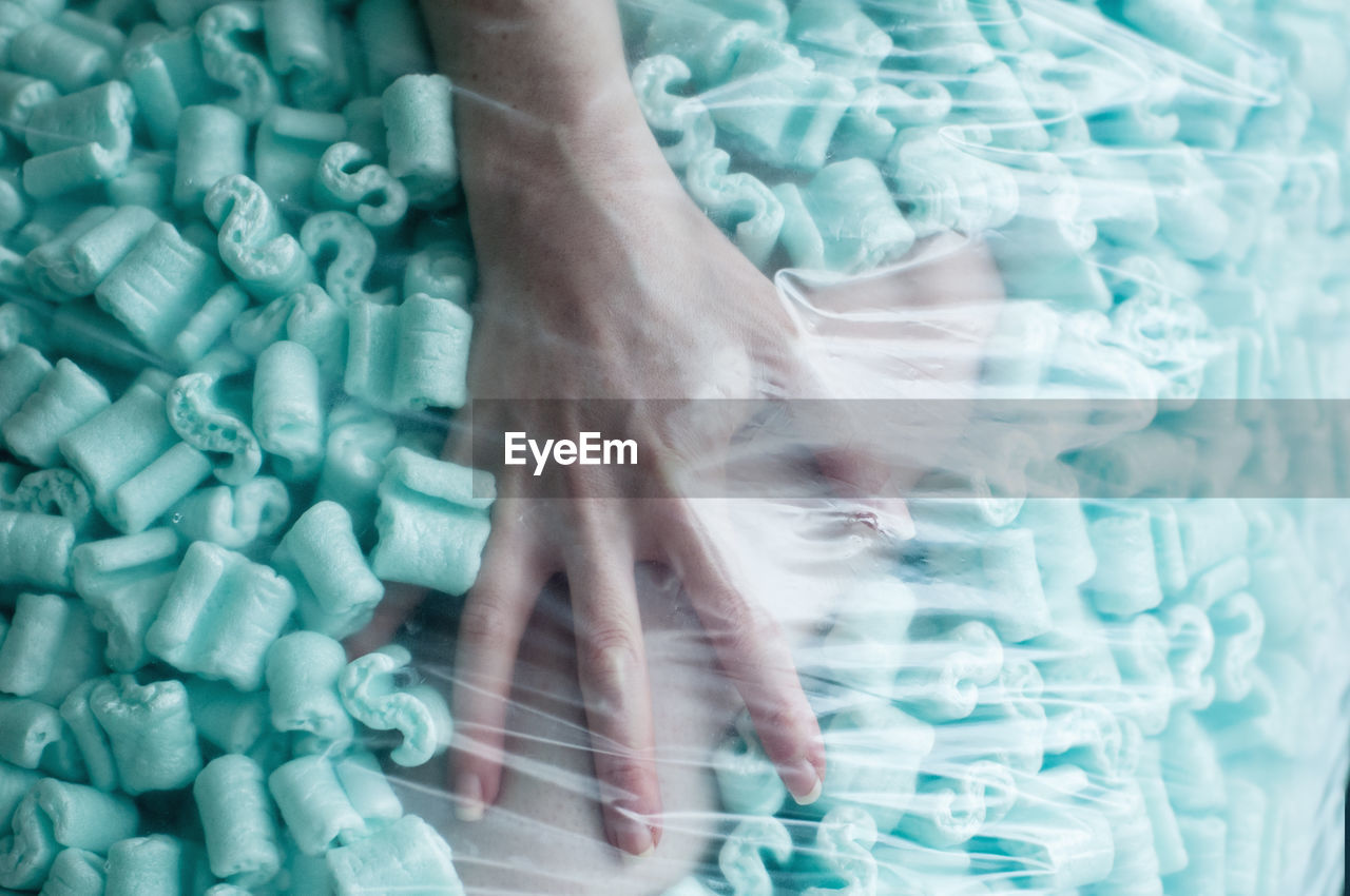 Cropped Hand Of Woman Amidst Sweet Food Seen Through Plastic