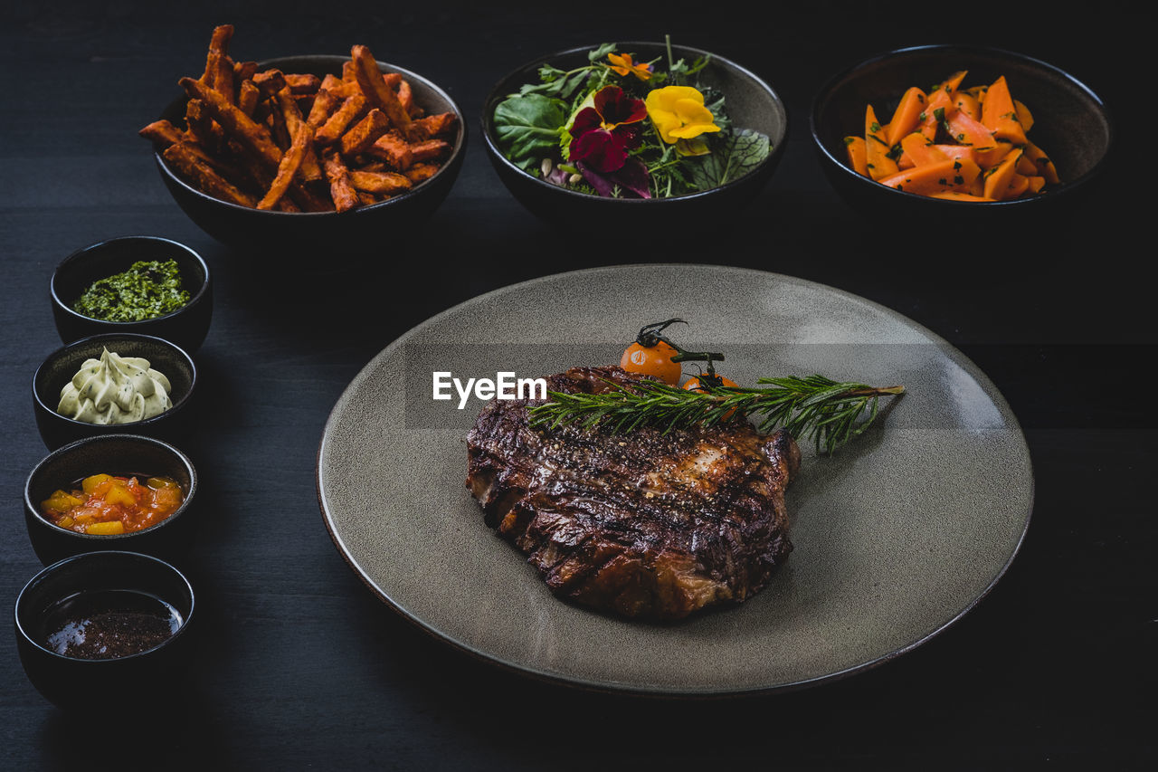 food and drink, food, ready-to-eat, freshness, meat, vegetable, plate, indoors, potato, table, no people, prepared potato, serving size, still life, healthy eating, french fries, salad, meal, bowl, red meat, beef, rib, dinner, garnish, temptation