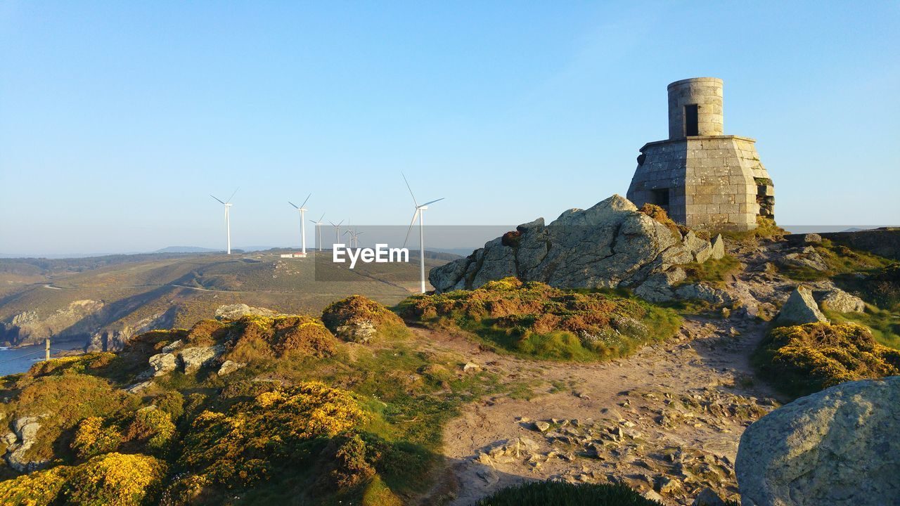 fuel and power generation, environmental conservation, sky, wind turbine, environment, turbine, renewable energy, alternative energy, mountain, nature, built structure, architecture, no people, day, wind power, beauty in nature, rock, clear sky, landscape, solid, outdoors