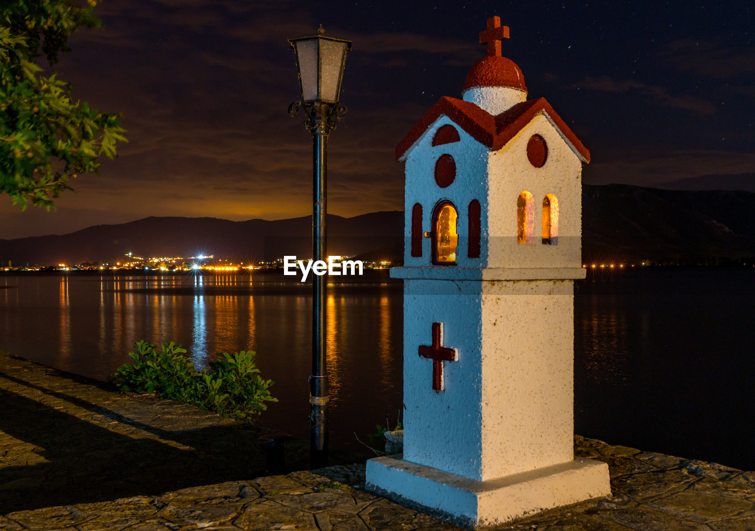 ILLUMINATED BUILDING BY LAKE AGAINST SKY