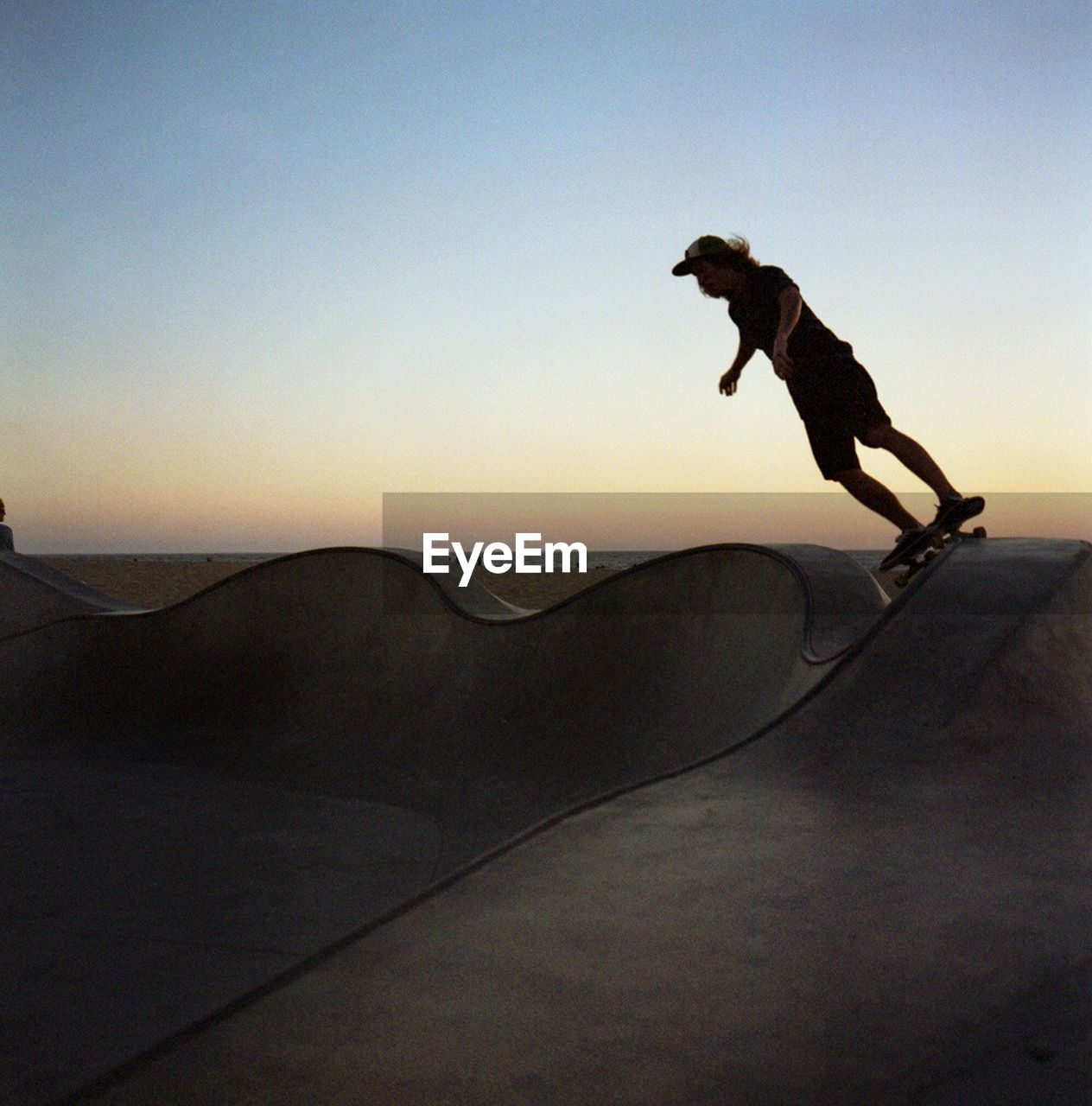 full length, jumping, one person, silhouette, outdoors, leisure activity, mid-air, adventure, fun, sunset, men, nature, skill, real people, skateboard park, clear sky, extreme sports, vacations, landscape, day, stunt, lifestyles, sport, sky, energetic, one man only, sand dune, young adult, people, adult
