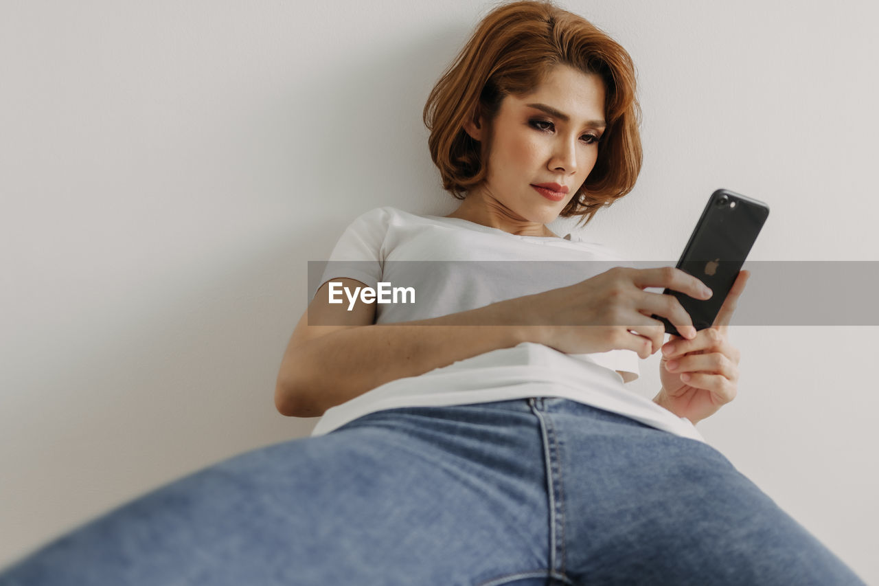 MIDSECTION OF WOMAN USING SMART PHONE WHILE SITTING ON MOBILE