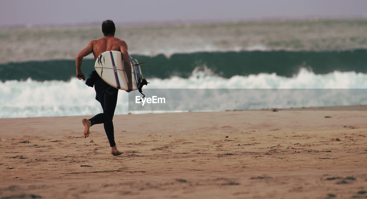Rear View Of Man With Surfboard Running At Beach