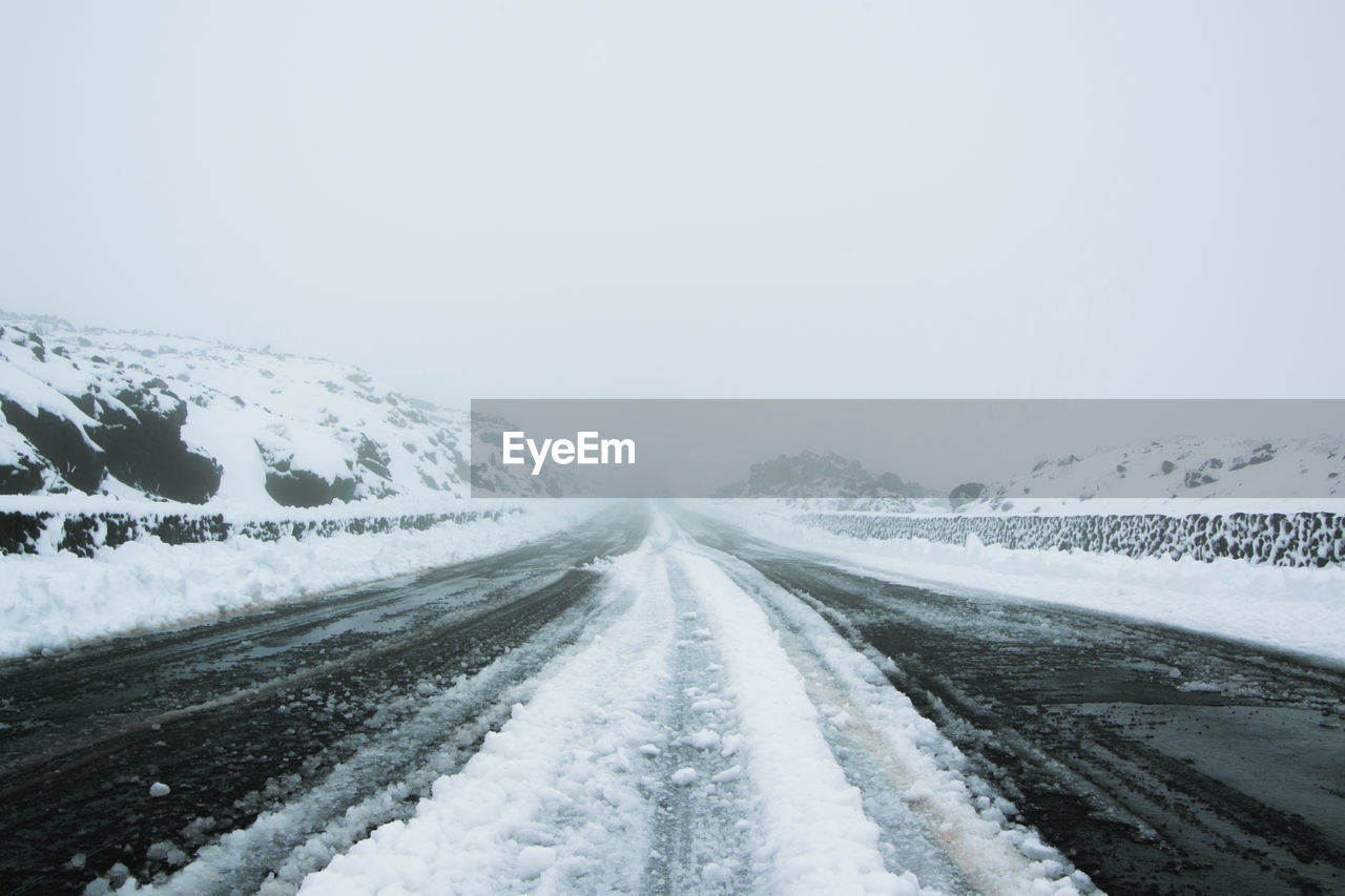 snow, cold temperature, winter, road, transportation, the way forward, sky, white color, copy space, nature, scenics - nature, no people, beauty in nature, tranquility, tranquil scene, environment, direction, day, landscape, diminishing perspective, extreme weather, outdoors, snowing, blizzard, snowcapped mountain