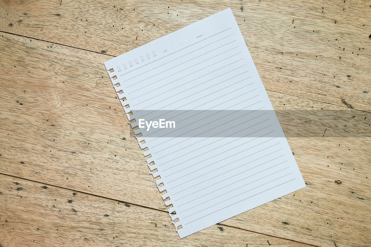 Directly above shot of blank white paper on wooden table