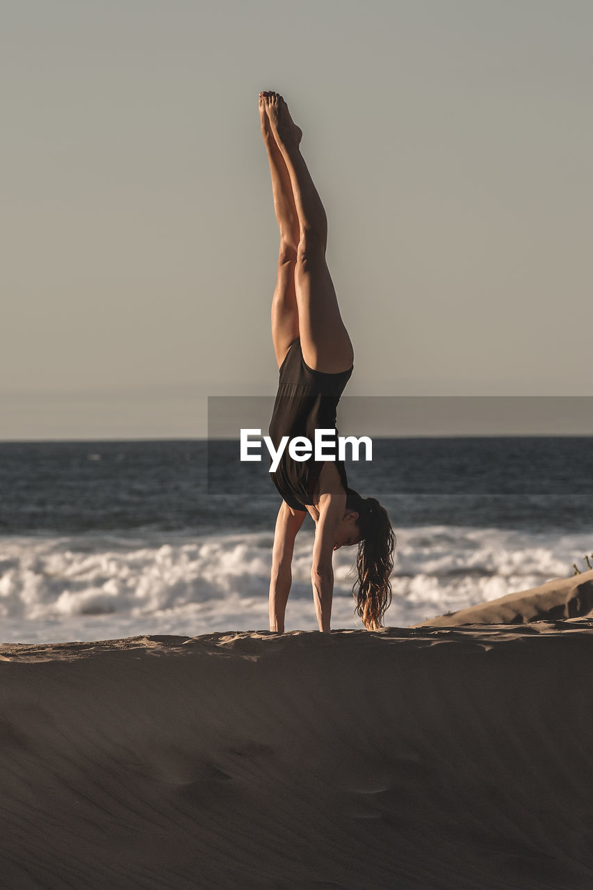 sea, land, sky, horizon over water, beach, leisure activity, balance, horizon, full length, real people, lifestyles, water, exercising, beauty in nature, flexibility, nature, sport, people, handstand, skill