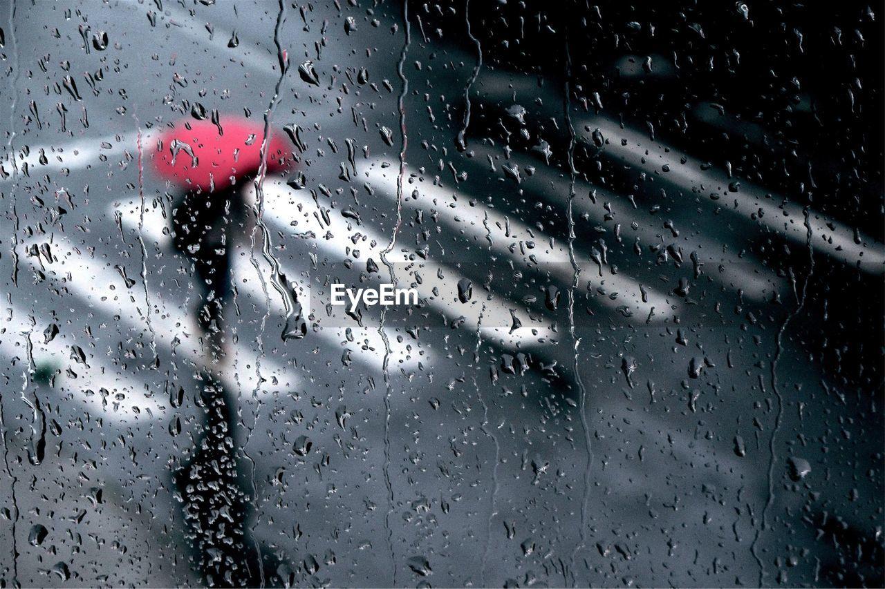 Person covering umbrella in raining season viewed through window