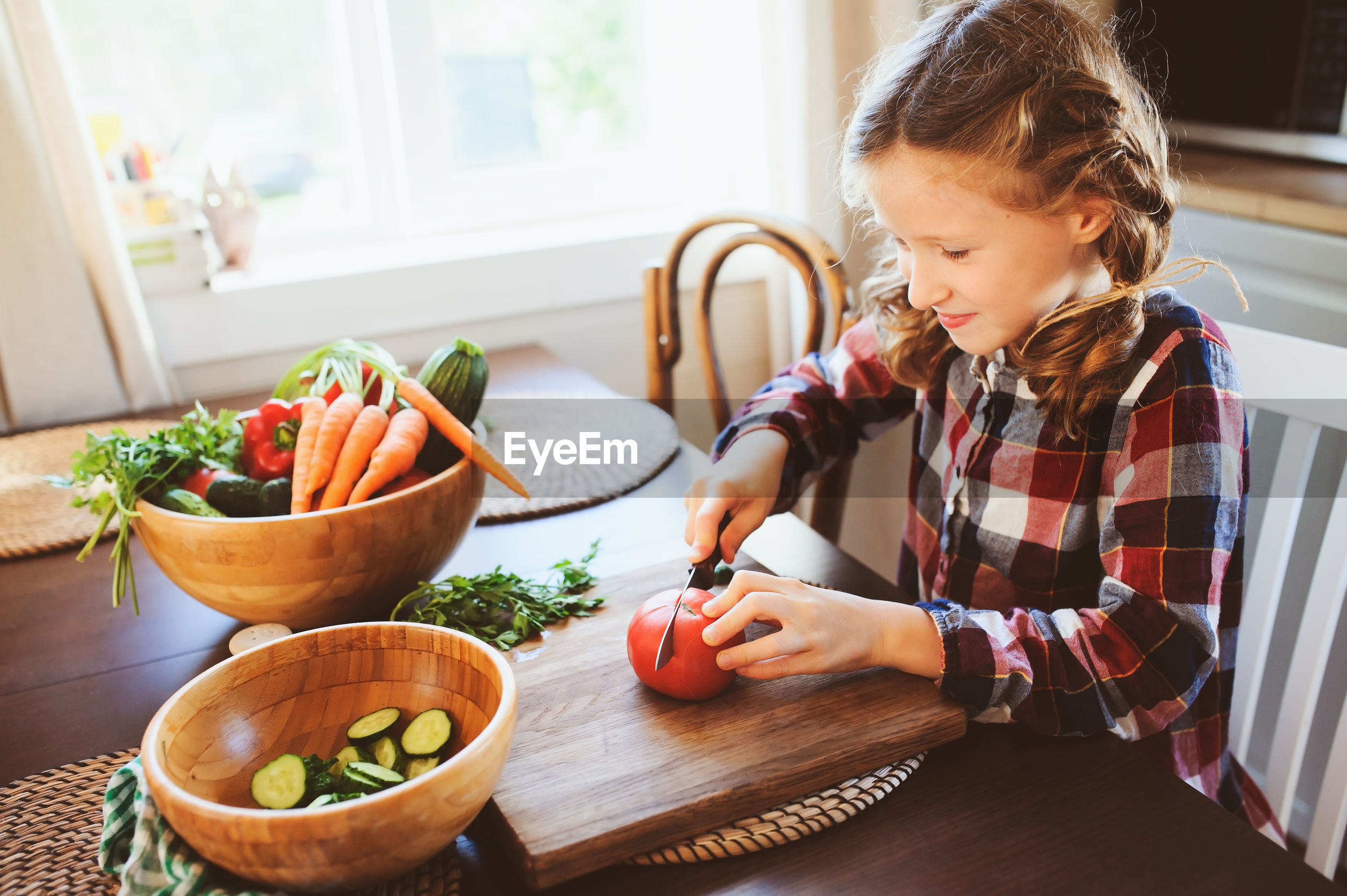 Girl cutting tomato on table in kitchen at home