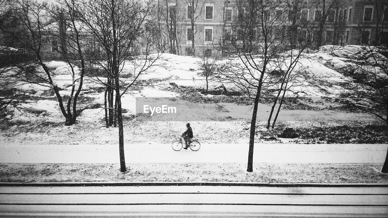 Man riding bicycle on road during winter