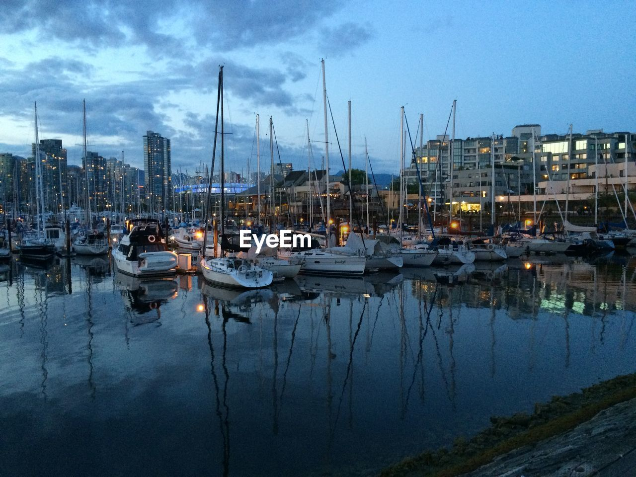 Sailboats Moored On Harbor By City Against Sky At Sunset