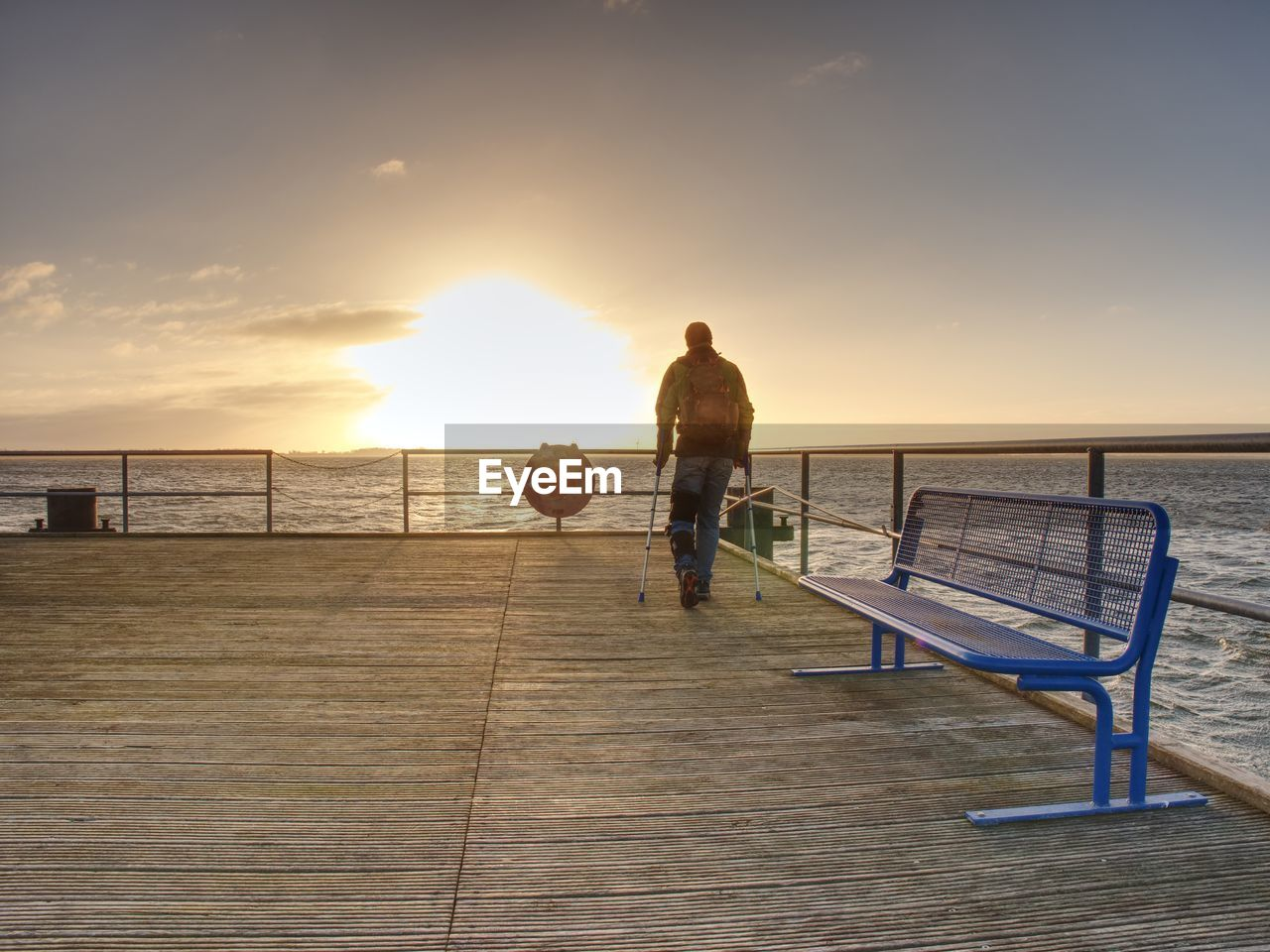 REAR VIEW OF MAN ON PIER AT SEA AGAINST SKY
