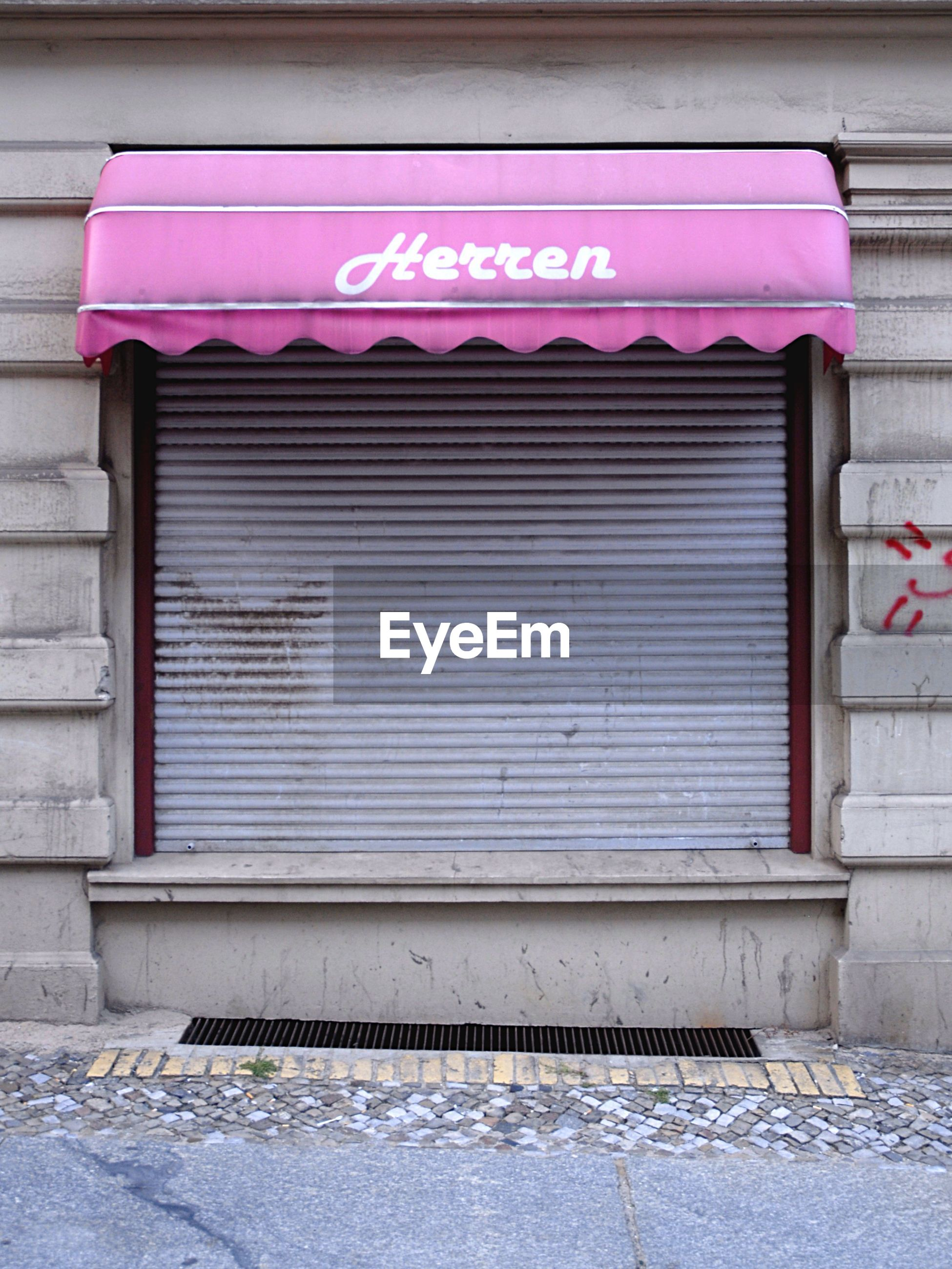 Closed shop with pink awning by sidewalk in city
