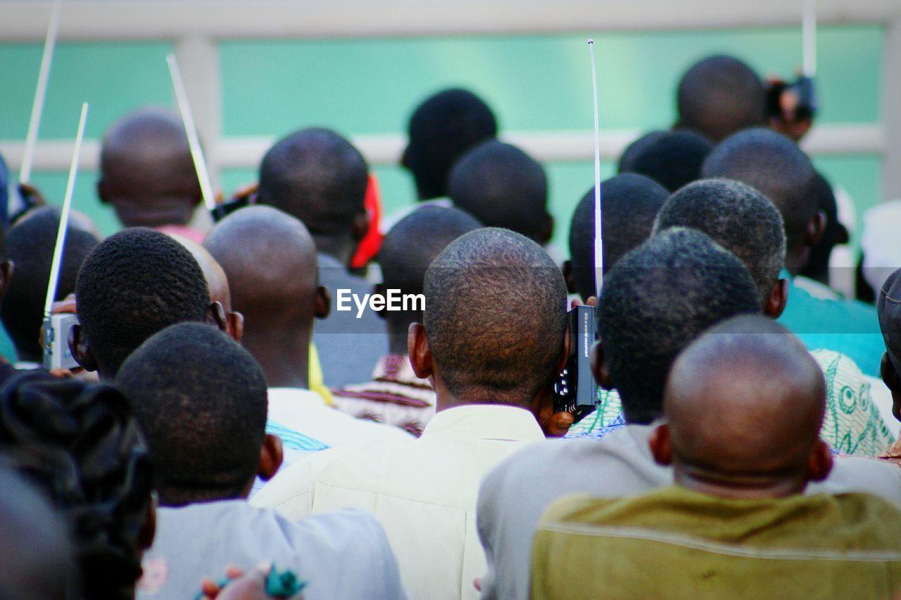Rear view of men listening to radio