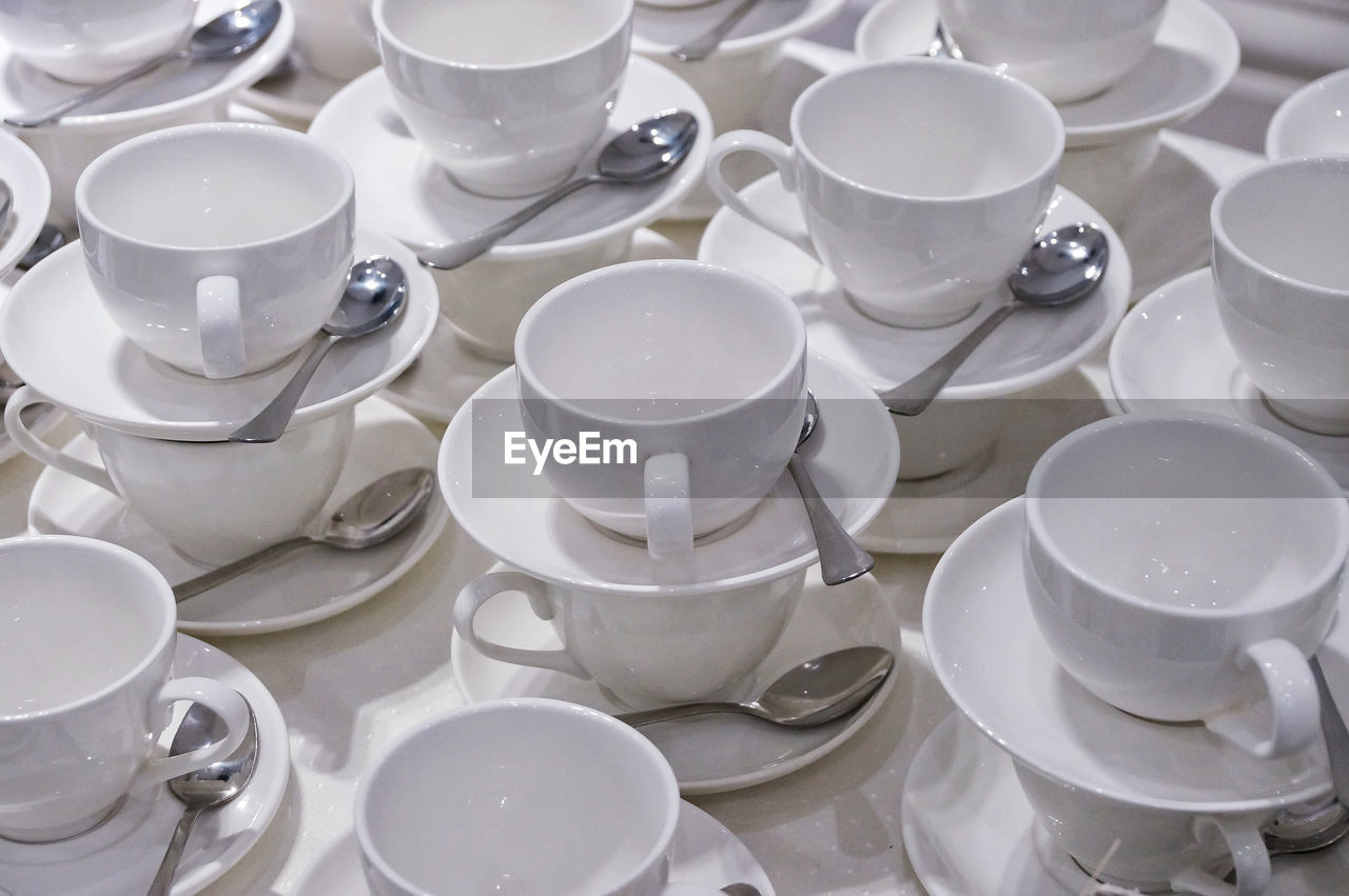 Full Frame Shot Of Empty Coffee Cups With Spoons
