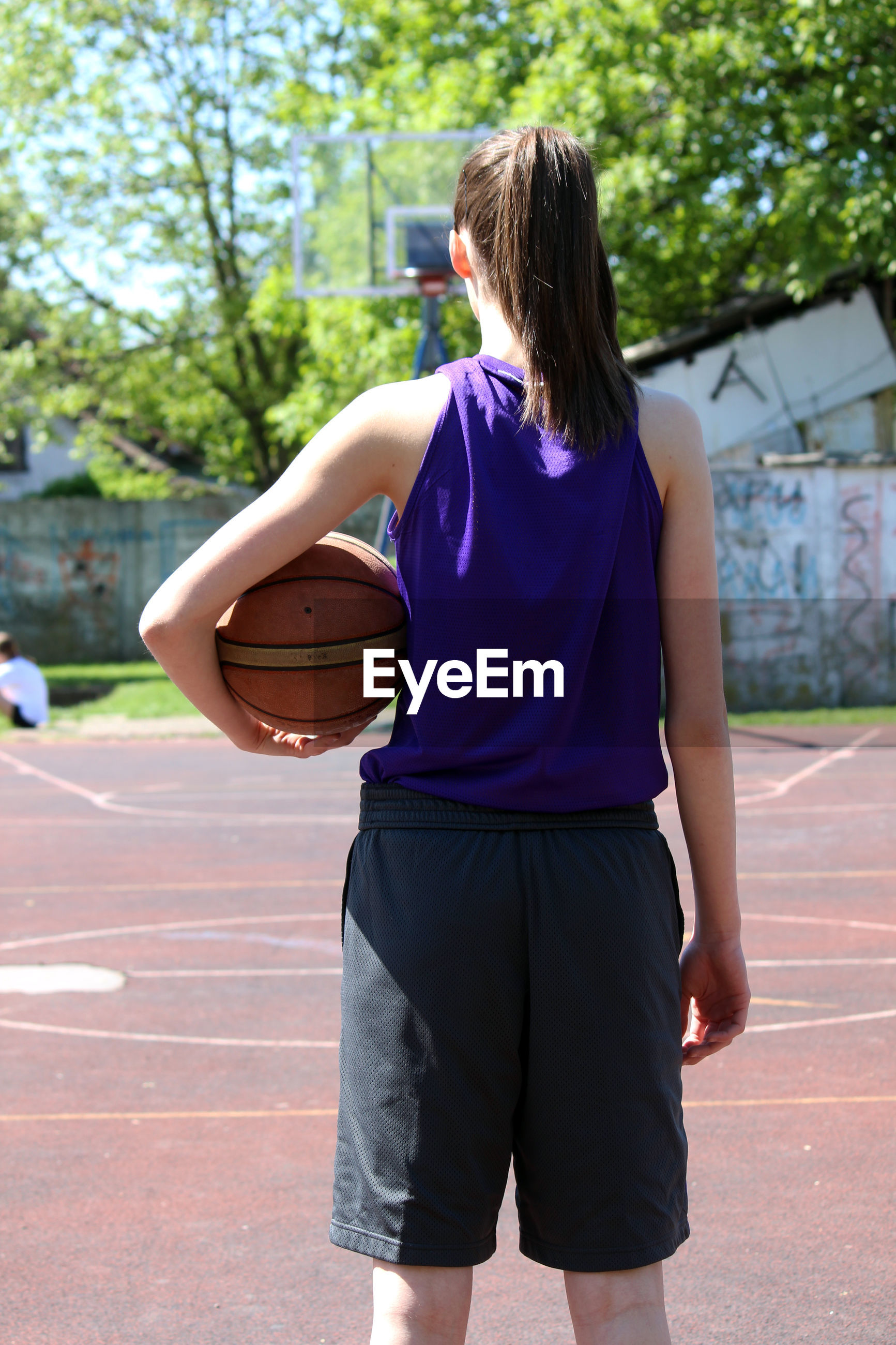 REAR VIEW OF WOMAN PLAYING WITH BALL ON BASKETBALL COURT