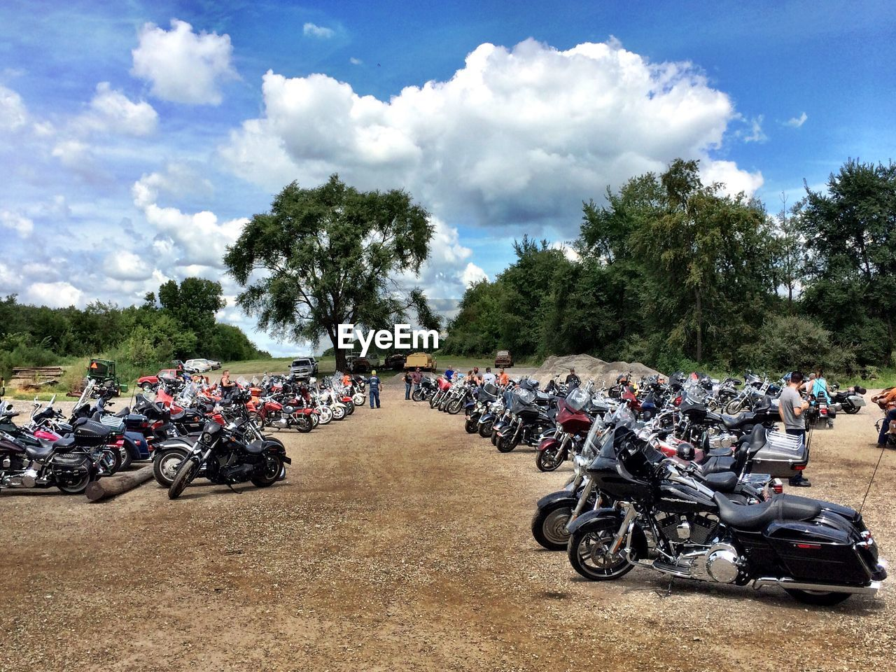 motorcycle, large group of people, crash helmet, real people, motorsport, mode of transport, sports race, sky, transportation, motorcycle racing, men, land vehicle, riding, biker, day, cloud - sky, outdoors, competition, lifestyles, sports helmet, tree, sports track, helmet, motocross, extreme sports, headwear, people