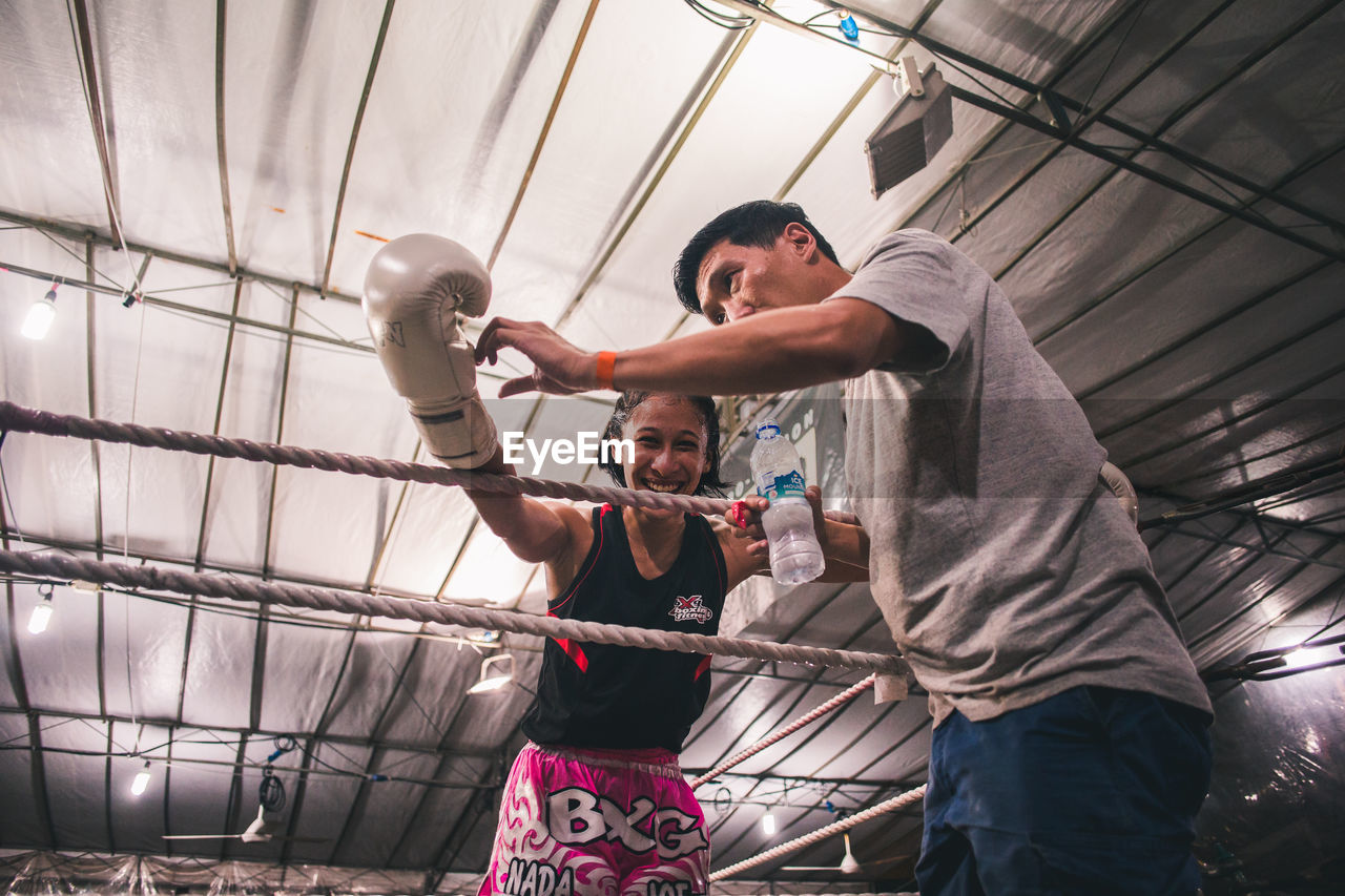 real people, indoors, low angle view, people, strength, lifestyles, men, sport, three quarter length, boxing - sport, young adult, adult, healthy lifestyle, young men, punching, standing, front view, casual clothing, effort, ceiling