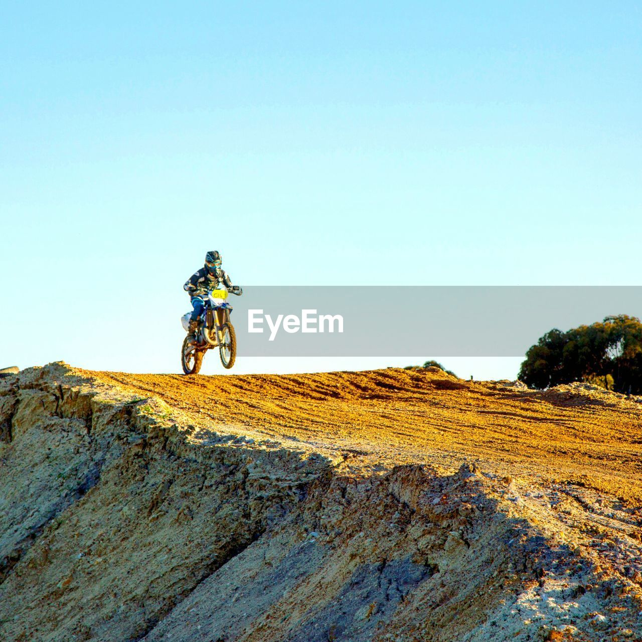 Low Angle View Of Motocross Biker On Track Against Sky