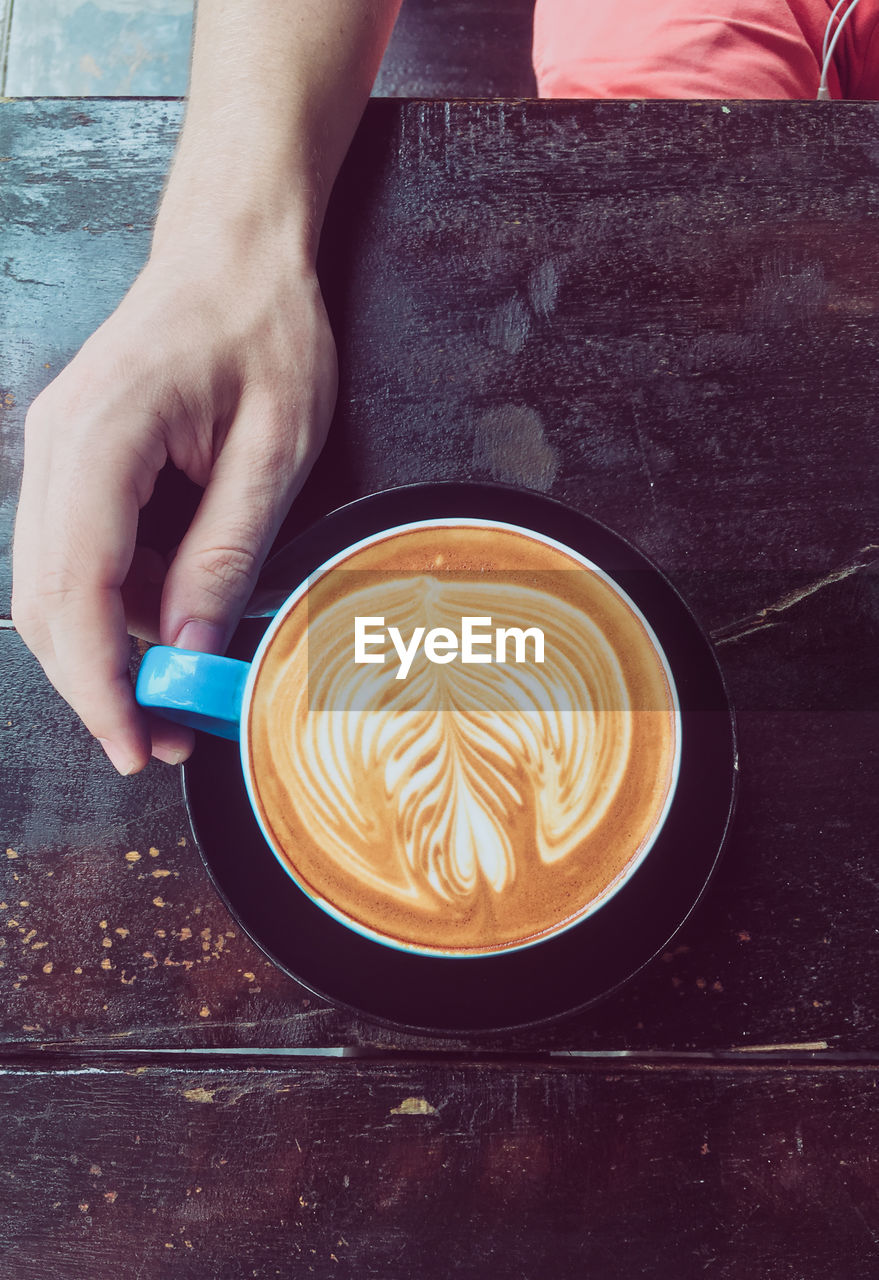 food and drink, drink, coffee, coffee - drink, refreshment, one person, coffee cup, human hand, frothy drink, cup, mug, froth art, table, hand, real people, freshness, cappuccino, indoors, hot drink, human body part, crockery, latte