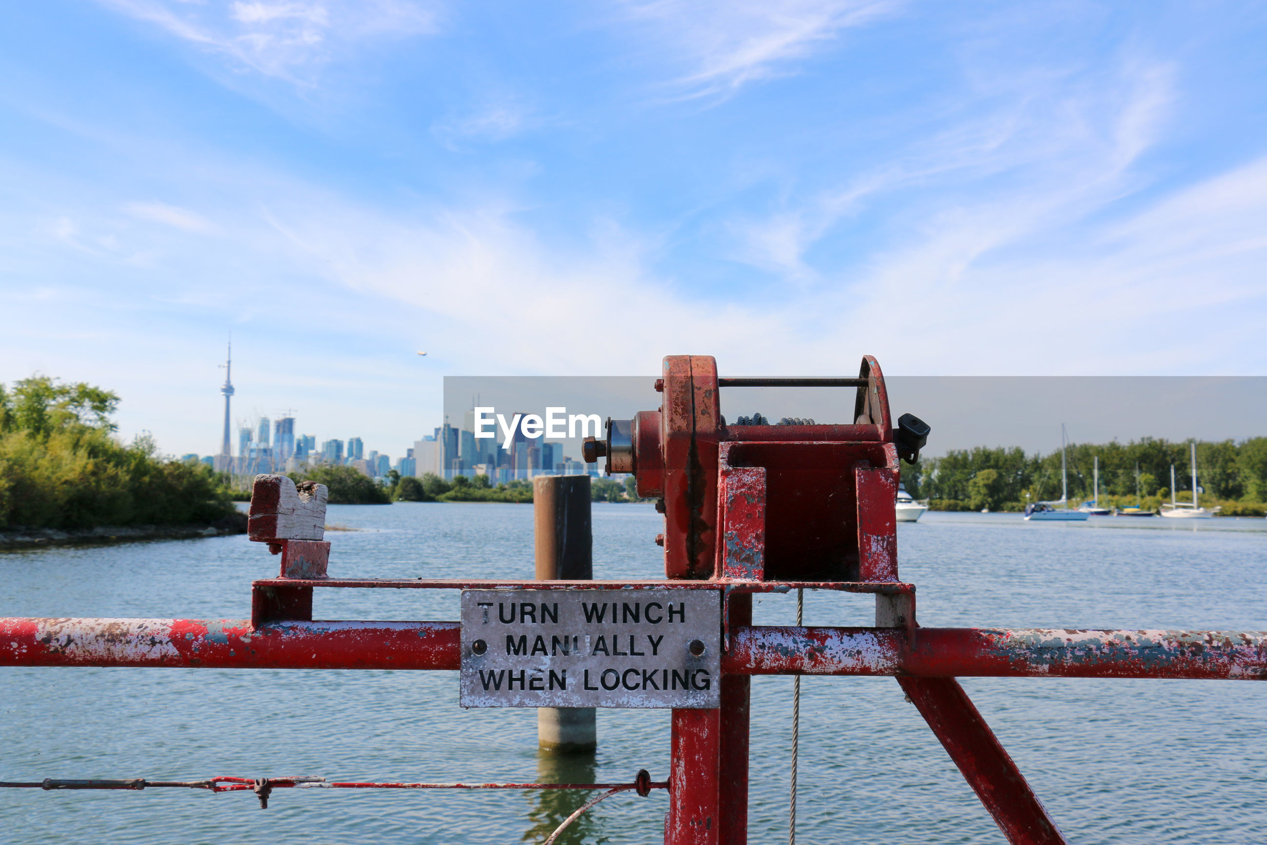 Cable winch with sign by sea against cn tower in city
