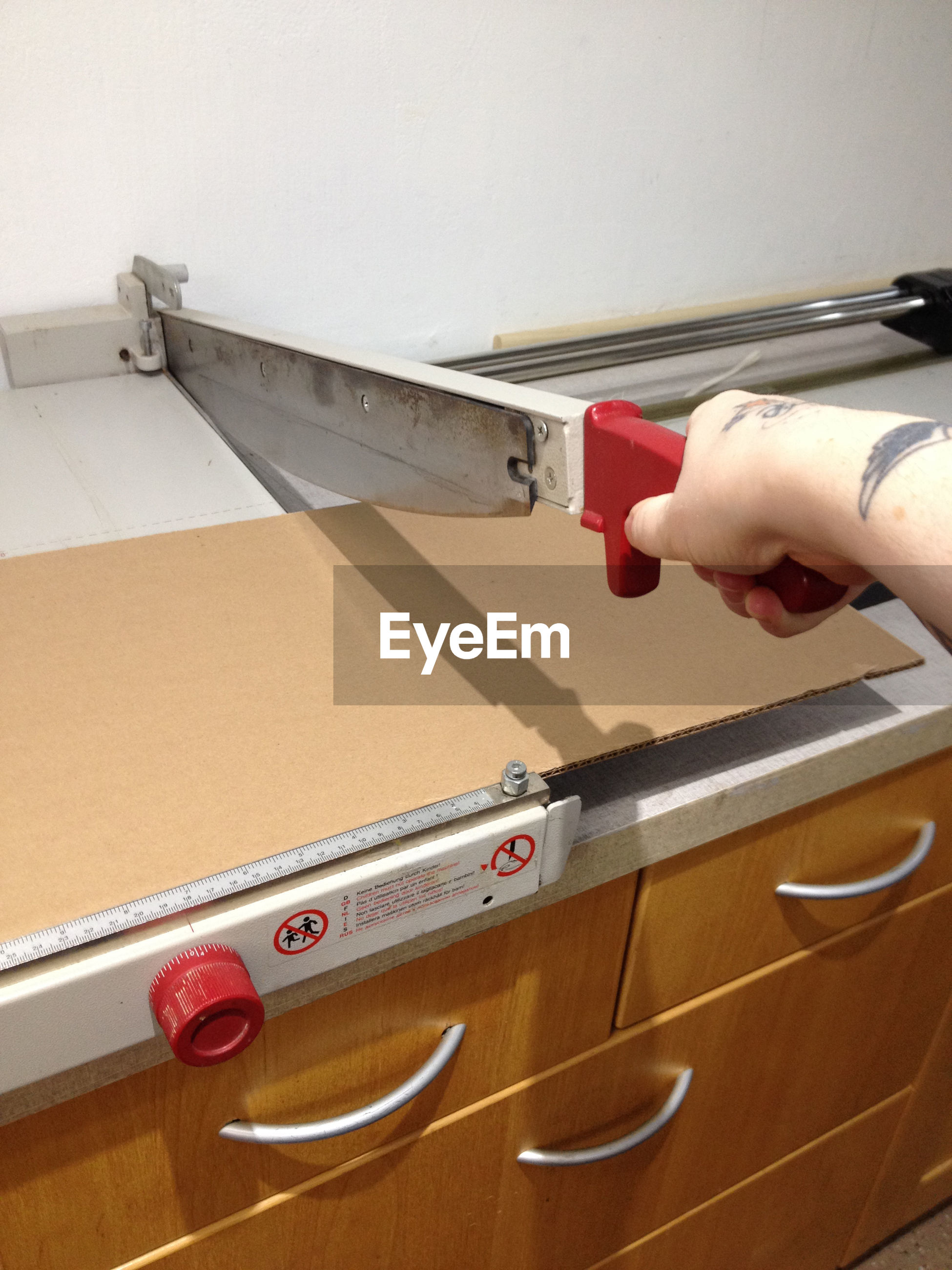 Cropped image of person using cardboard cutting machine