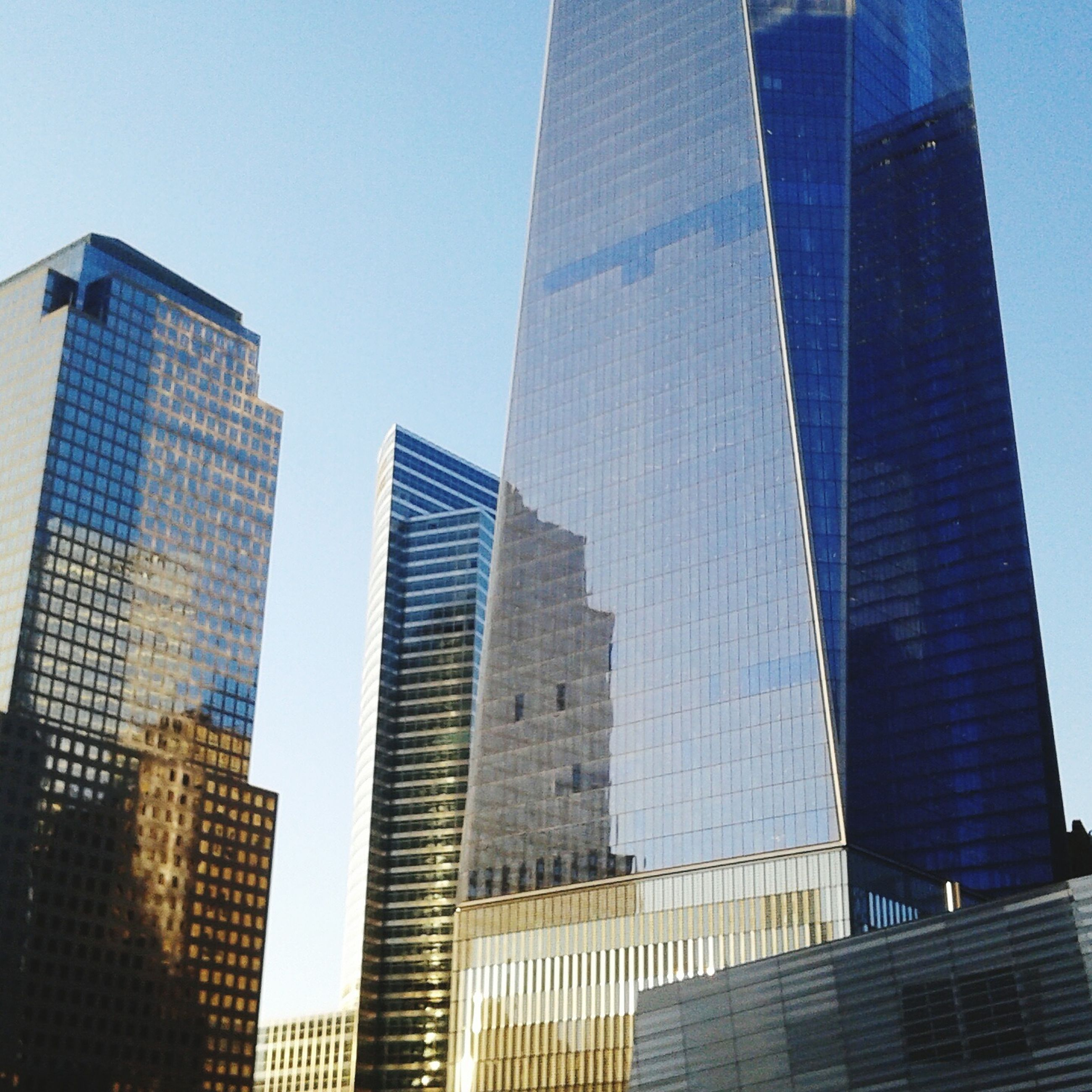 building exterior, architecture, built structure, skyscraper, city, modern, tall - high, office building, tower, low angle view, building, clear sky, glass - material, financial district, tall, sky, city life, urban skyline, capital cities, reflection