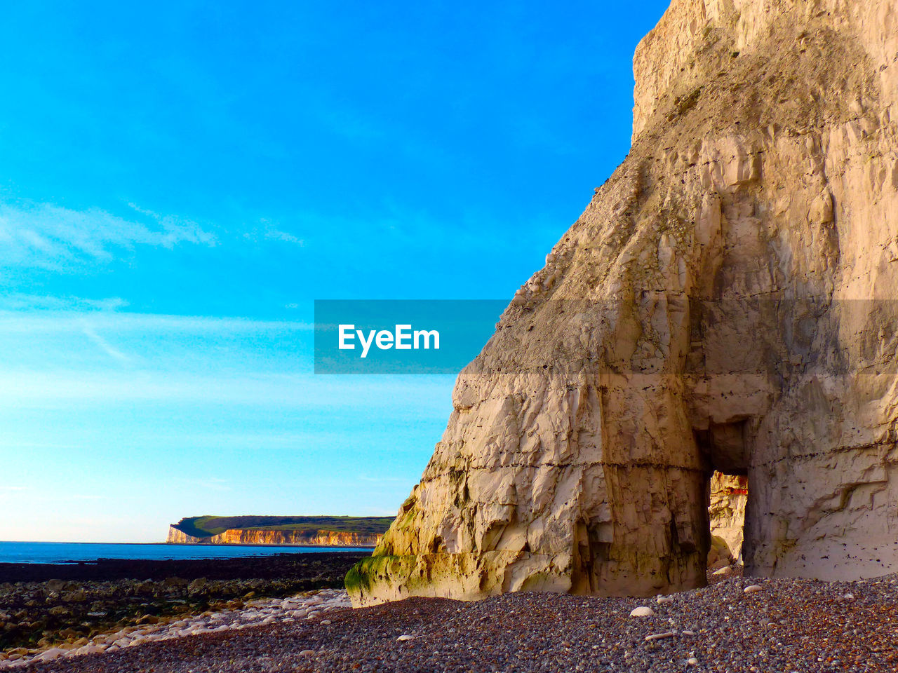 VIEW OF ROCK FORMATION BY SEA AGAINST SKY