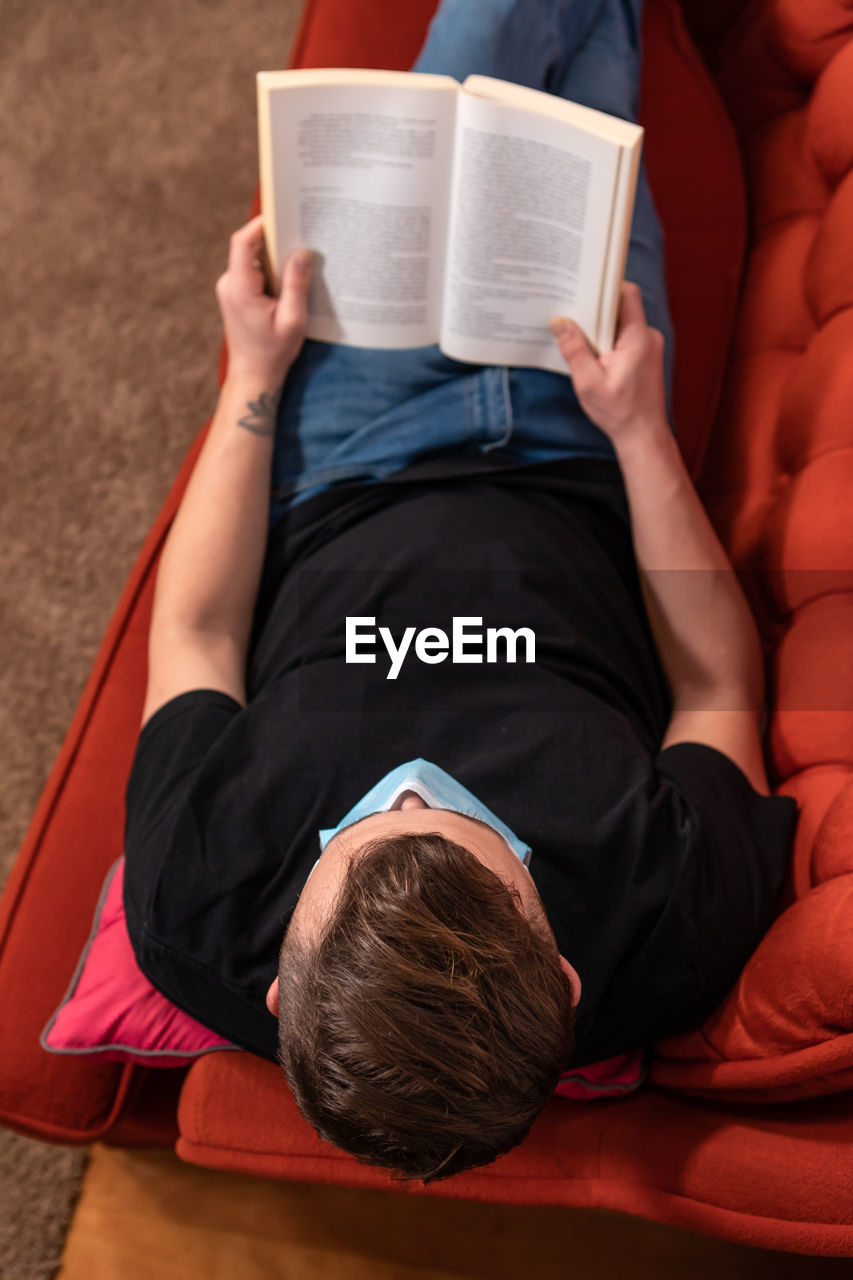 HIGH ANGLE VIEW OF MAN SITTING ON BOOK WITH BOOKS