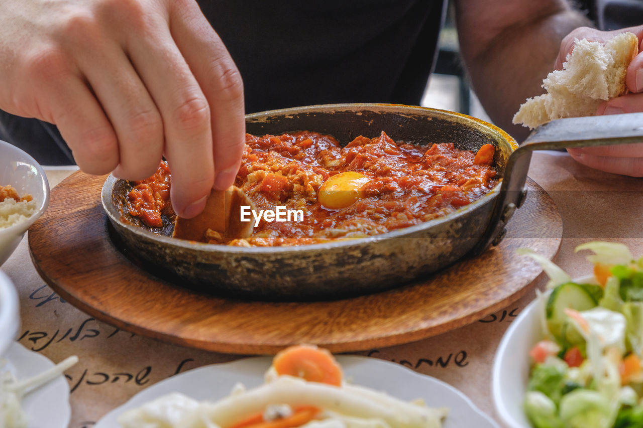 Close-up of person eating shakshouka on table