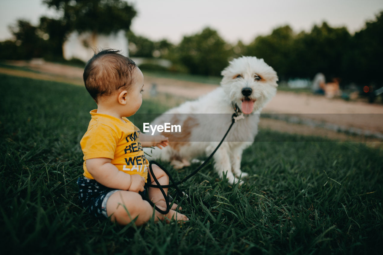 Full length of a child and dog on field