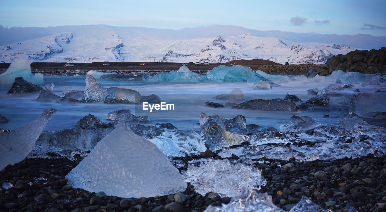 Close-up of ice on shore at beach during winter