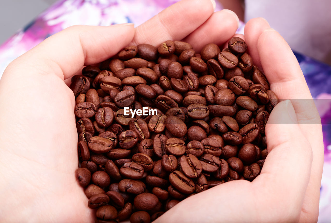 Close-Up Of Hands Holding Coffee Beans