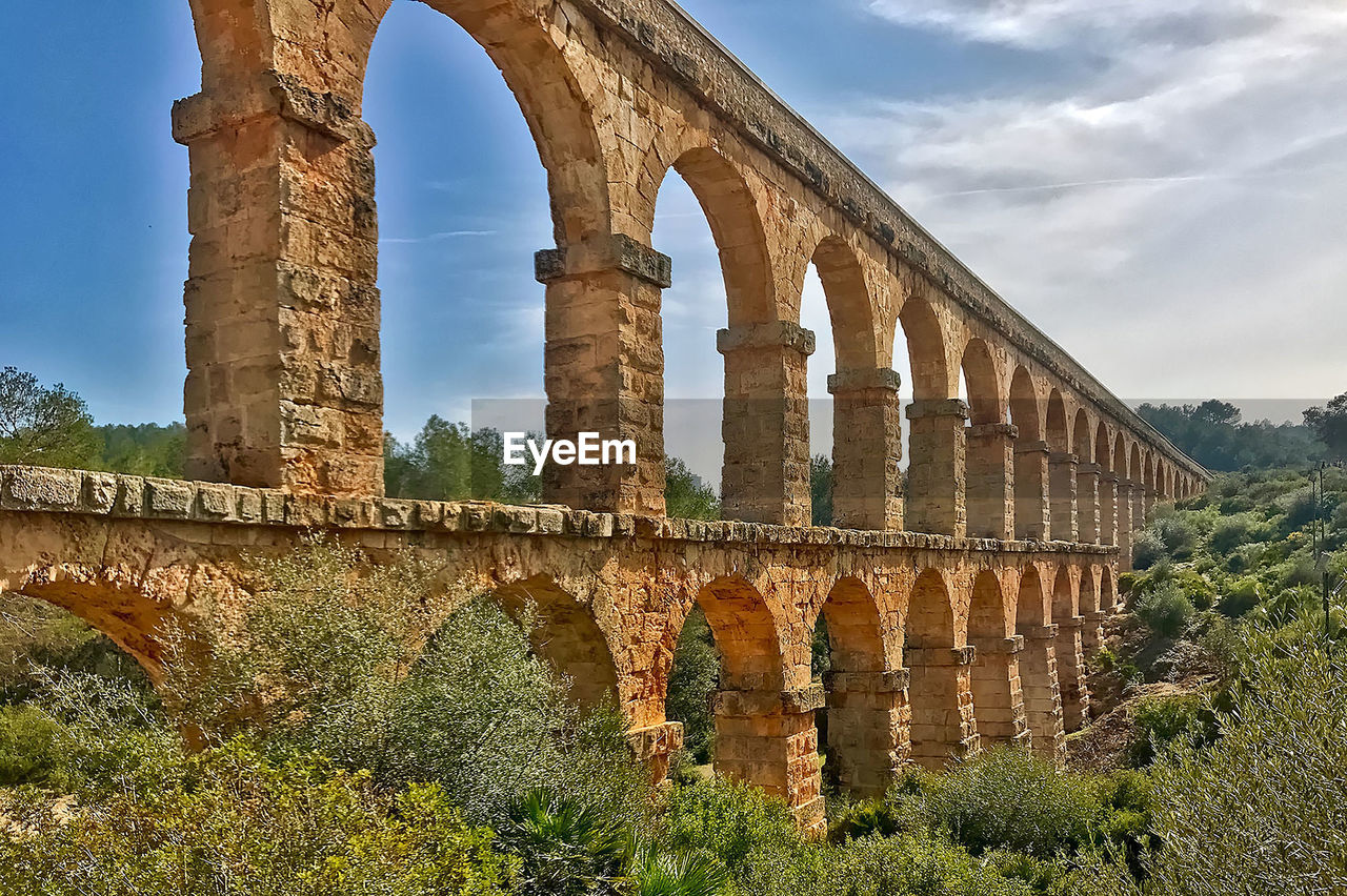 architecture, arch, history, old ruin, built structure, low angle view, day, architectural column, ancient, sky, cloud - sky, ancient civilization, archaeology, outdoors, bridge - man made structure, travel destinations, no people, tree, nature
