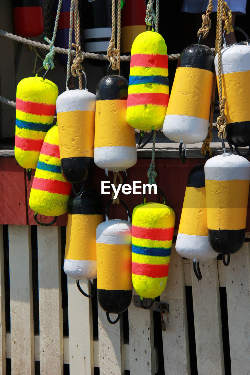 multi colored, hanging, no people, choice, close-up, variation, day, rope, outdoors, wood - material, safety, buoy, still life, for sale, protection, security, yellow, retail, side by side, striped