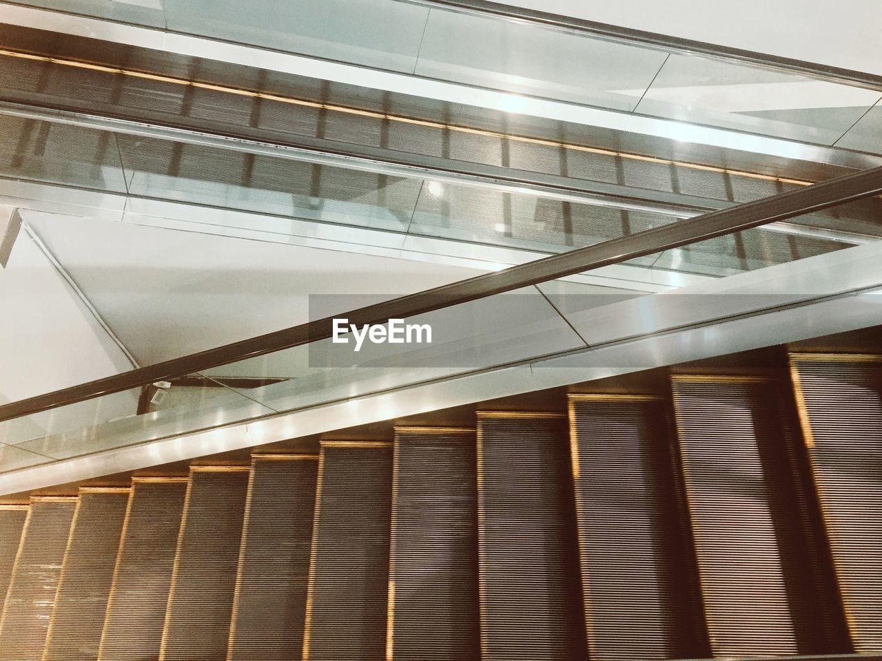 architecture, staircase, railing, built structure, steps and staircases, low angle view, indoors, modern, no people, building, illuminated, pattern, metal, escalator, connection, glass - material, day, ceiling, roof beam