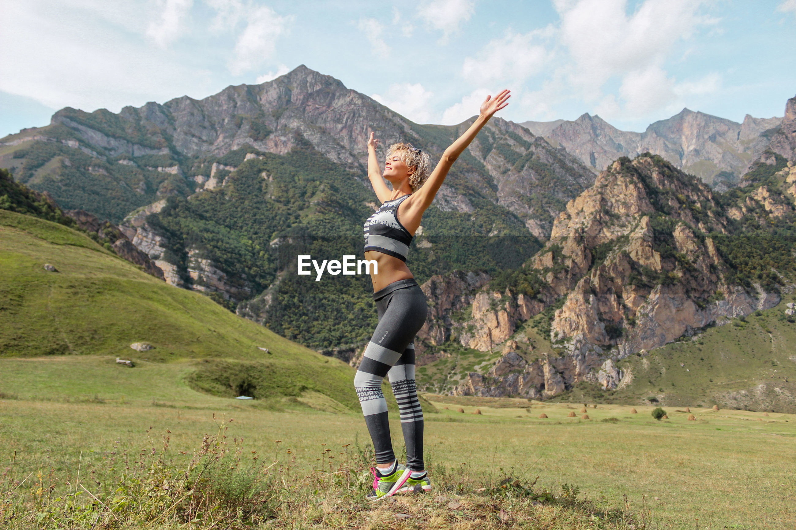 Woman in sports clothes with arms raised on mountain against sky