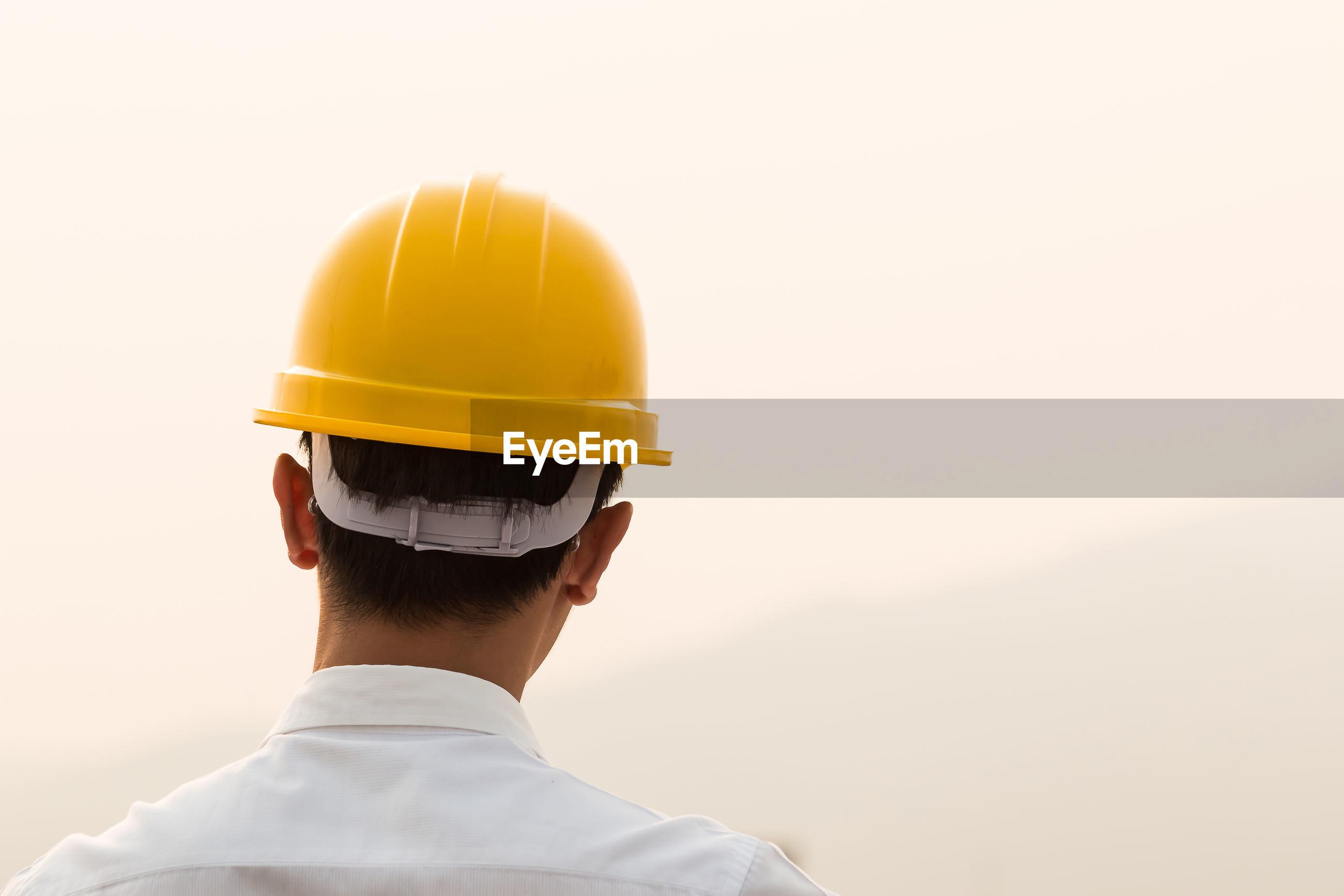 Rear view of engineer wearing hardhat against sky