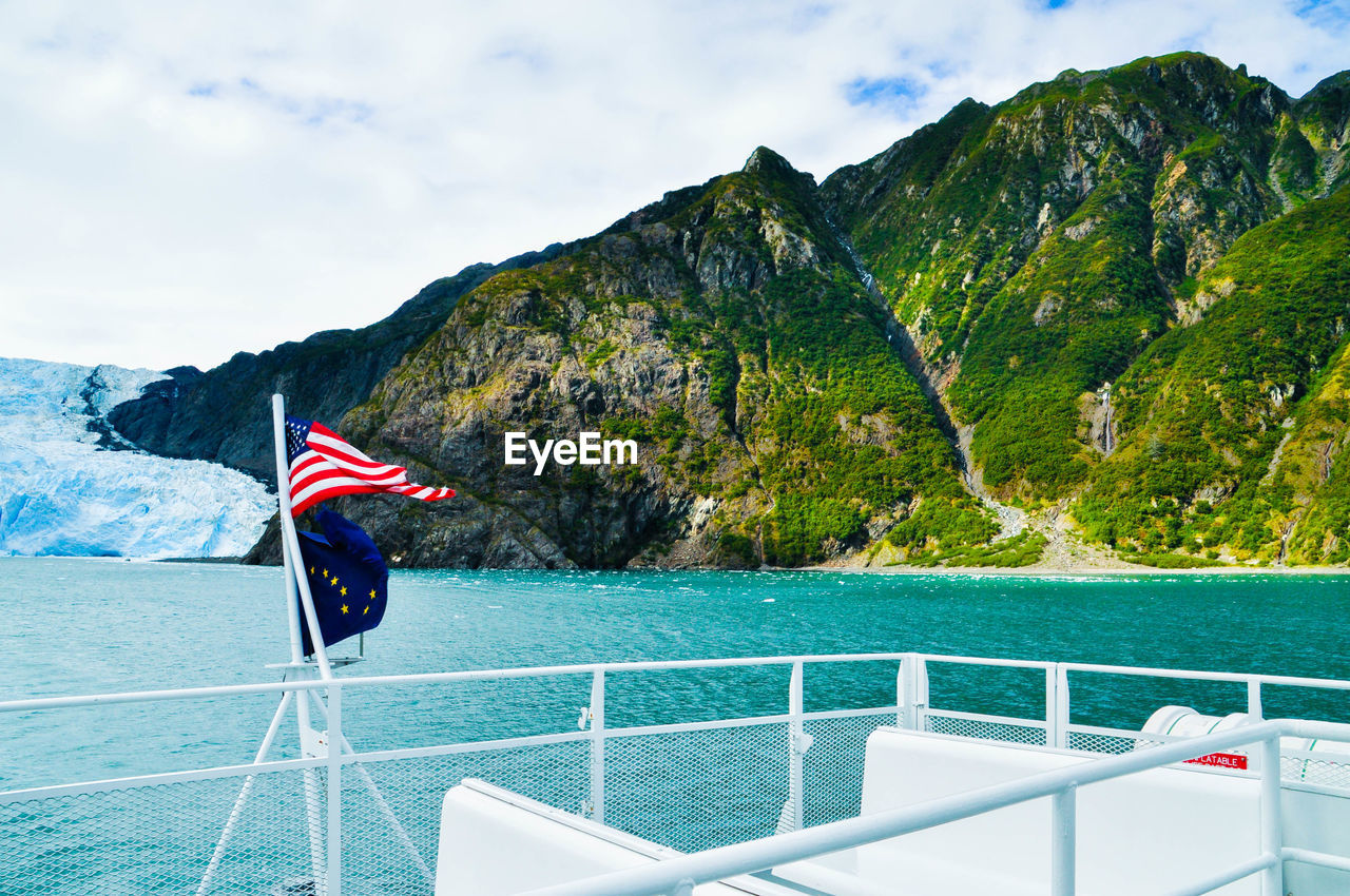 Scenic View Of Flag On Boat Against Sky