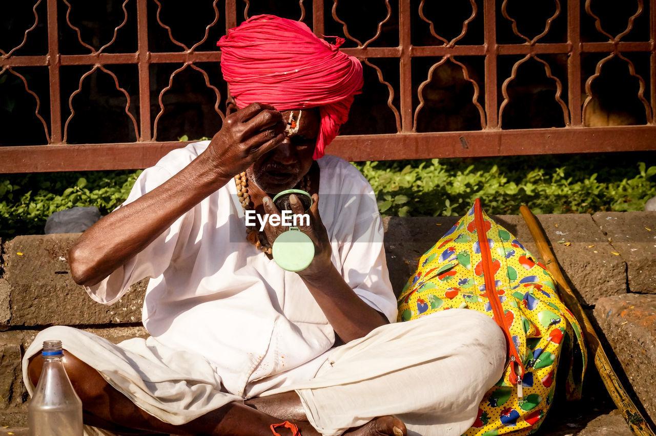 Sadhu Applying Tilaka While Sitting On Sidewalk