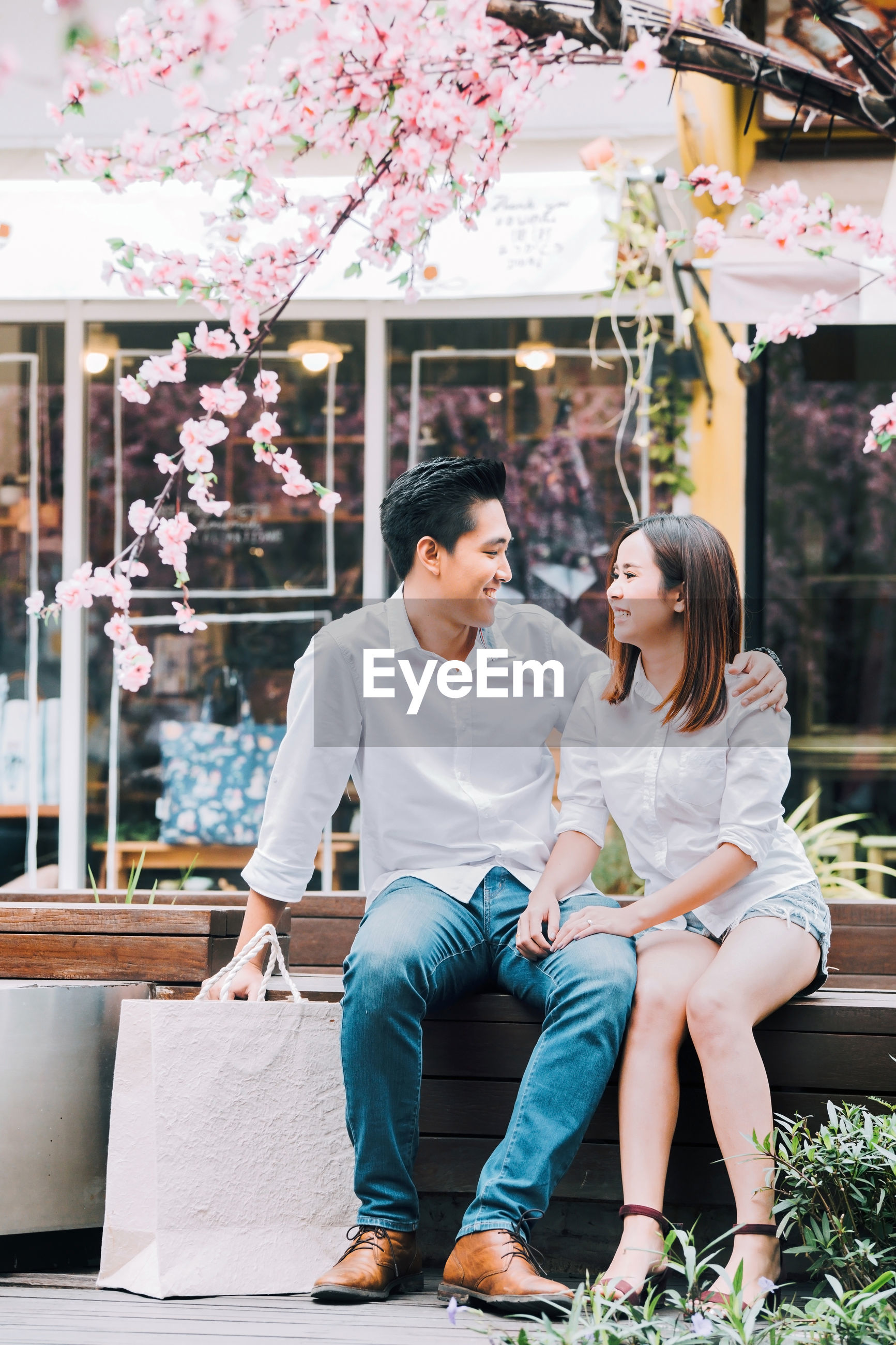 Smiling couple looking at each other while sitting on bench