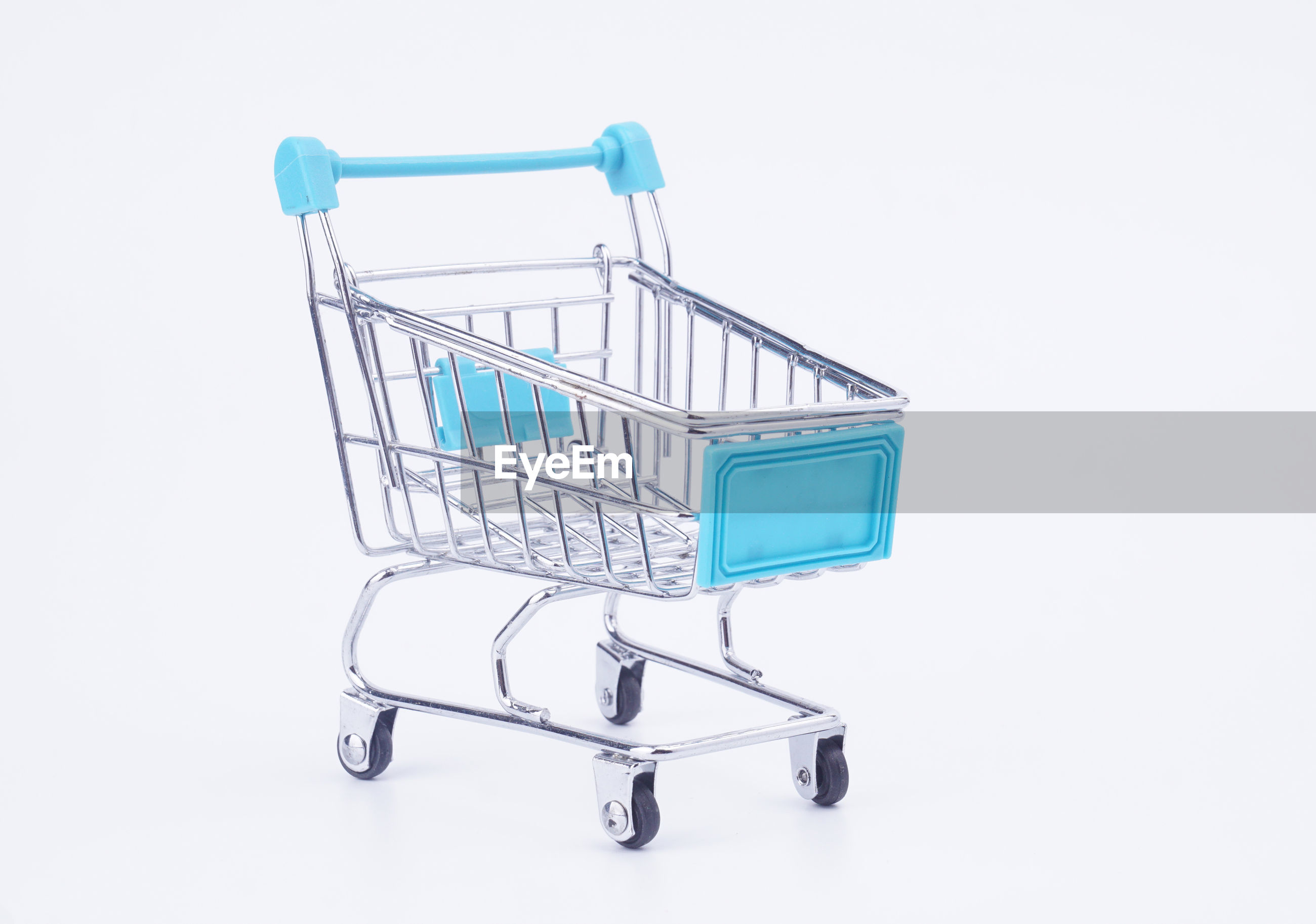 Close-up of miniature shopping cart against white background