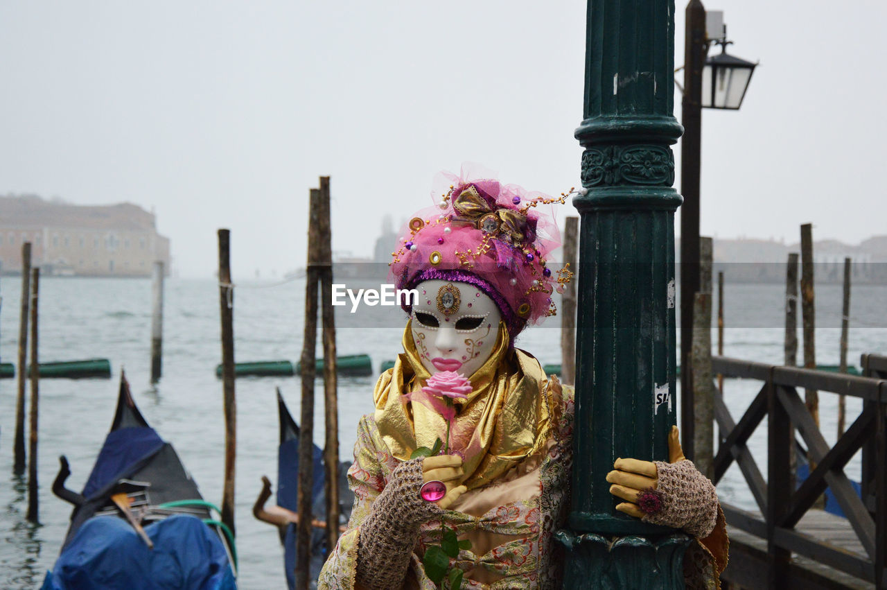 mask - disguise, venetian mask, real people, day, outdoors, focus on foreground, one person, leisure activity, tradition, gondola - traditional boat, clear sky, water, nautical vessel, standing, sea, nature, people