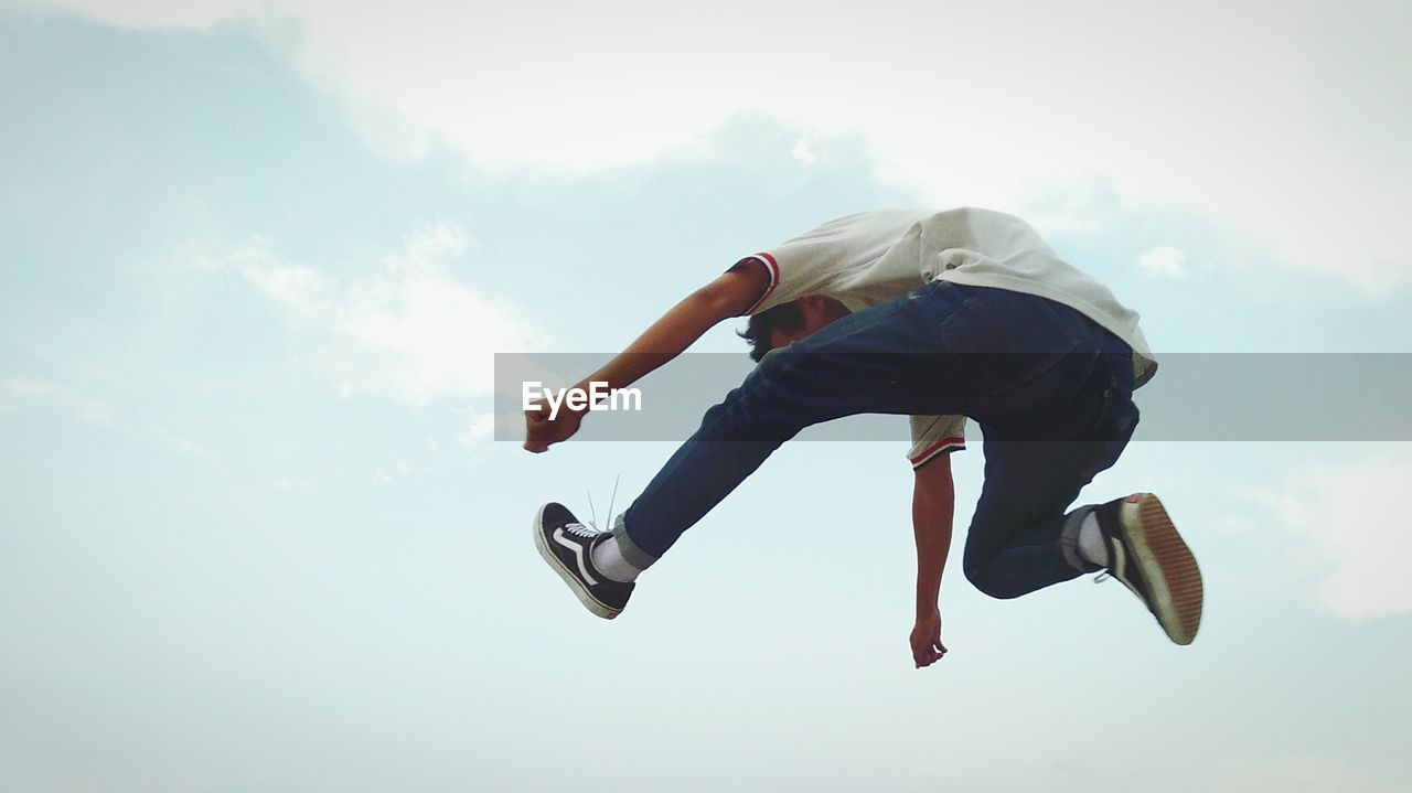 full length, mid-air, one person, jumping, low angle view, sky, energetic, real people, day, outdoors, childhood, people
