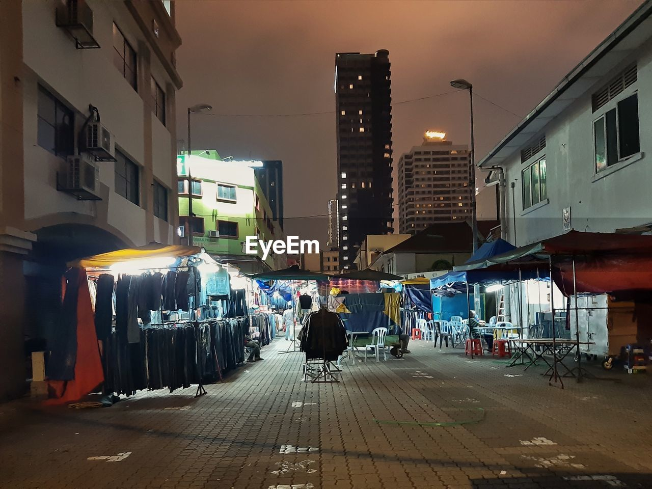 city, building exterior, architecture, built structure, street, illuminated, the way forward, direction, real people, transportation, sky, night, building, city life, incidental people, footpath, lighting equipment, lifestyles, outdoors, road