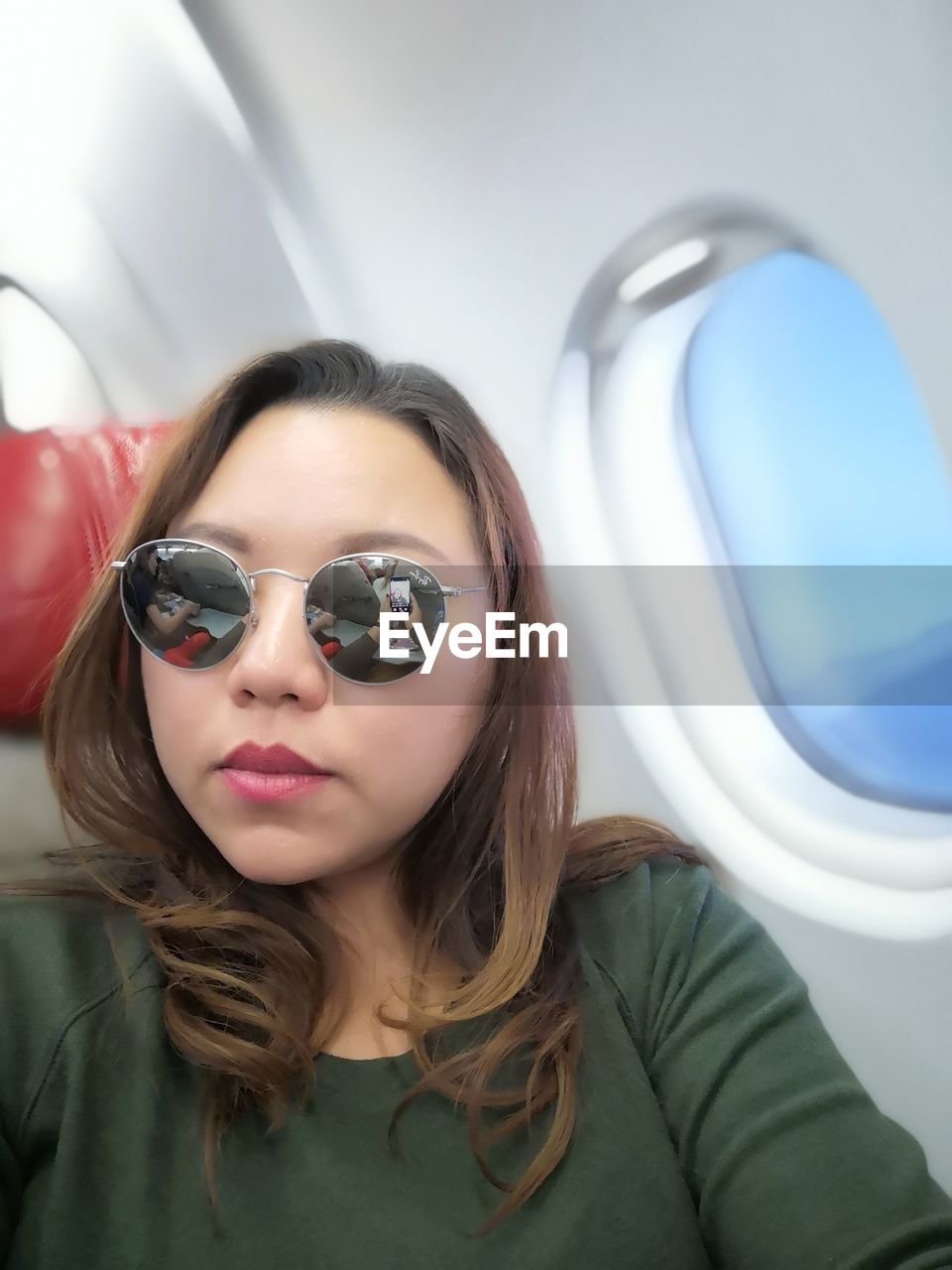 Portrait of woman wearing sunglasses while sitting in airplane
