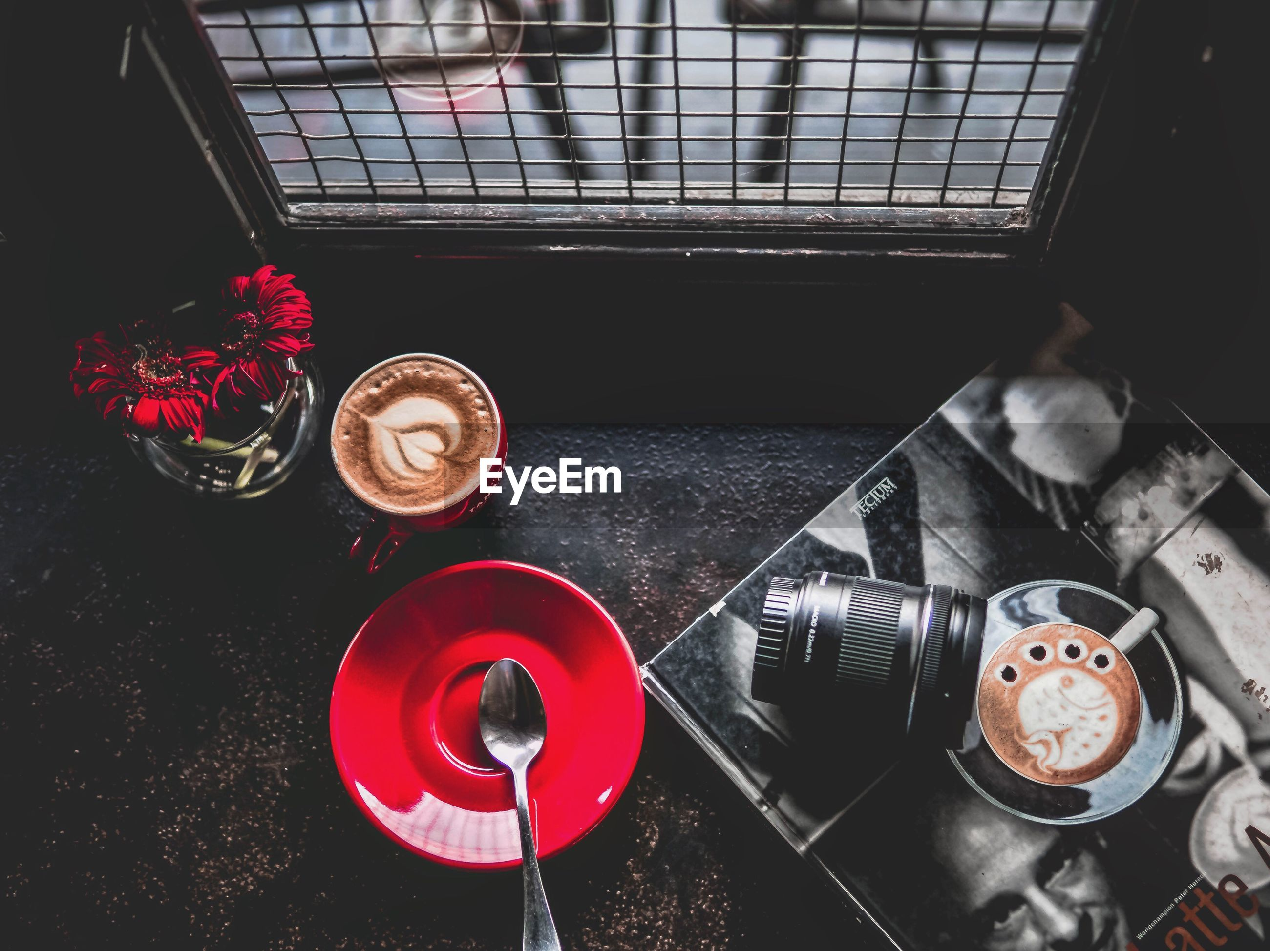 High angle view of coffee with flowers and camera lens on table
